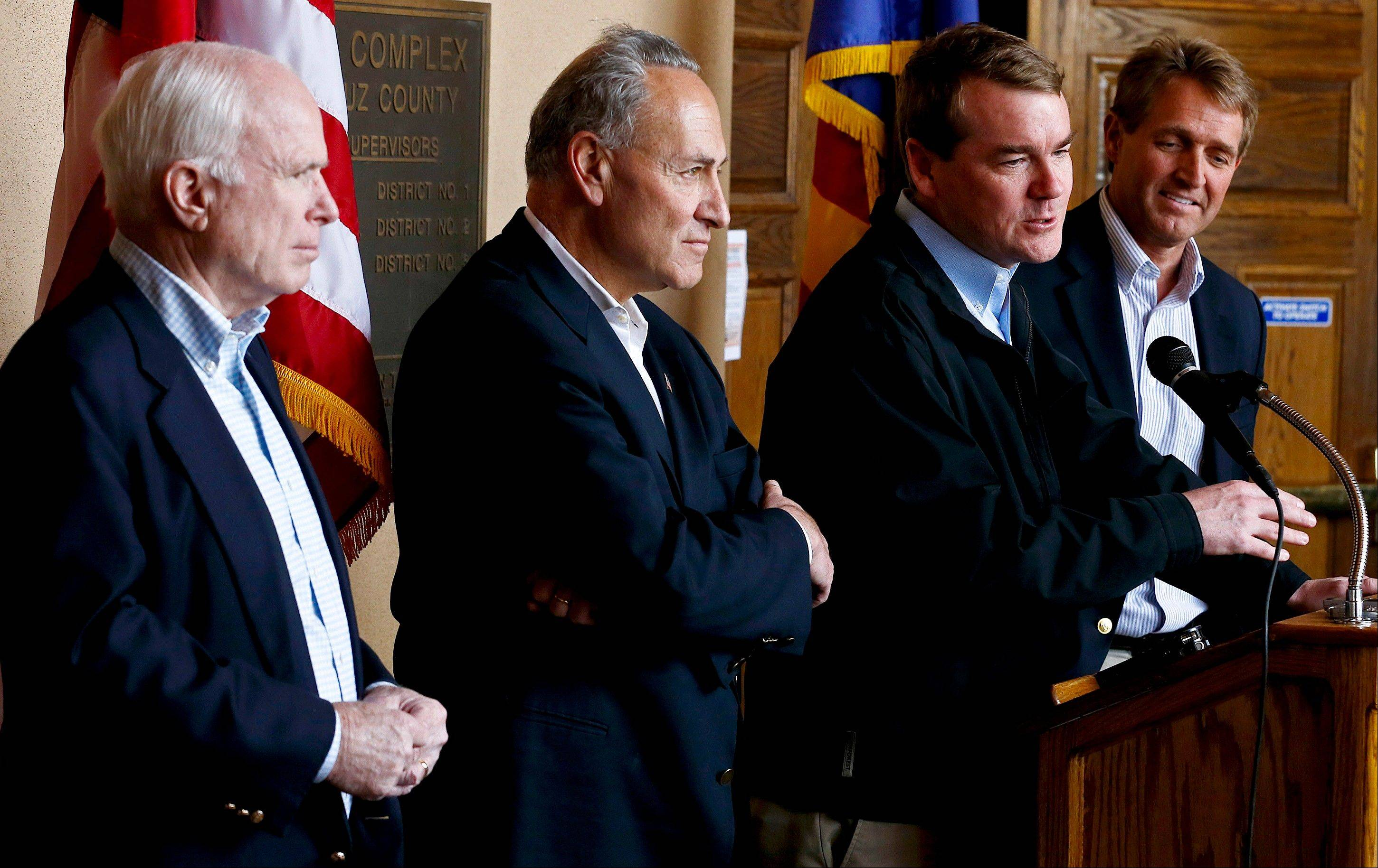 Colorado Democratic Sen. Michael Bennett, second right, speaks, as, from left, Sen. John McCain, R-Ariz., Sen. Chuck Schumer, D-N.Y., and Sen. Jeff Flake, R-Ariz., listen during a news conference after their tour of the Mexico border with the United States on Wednesday.