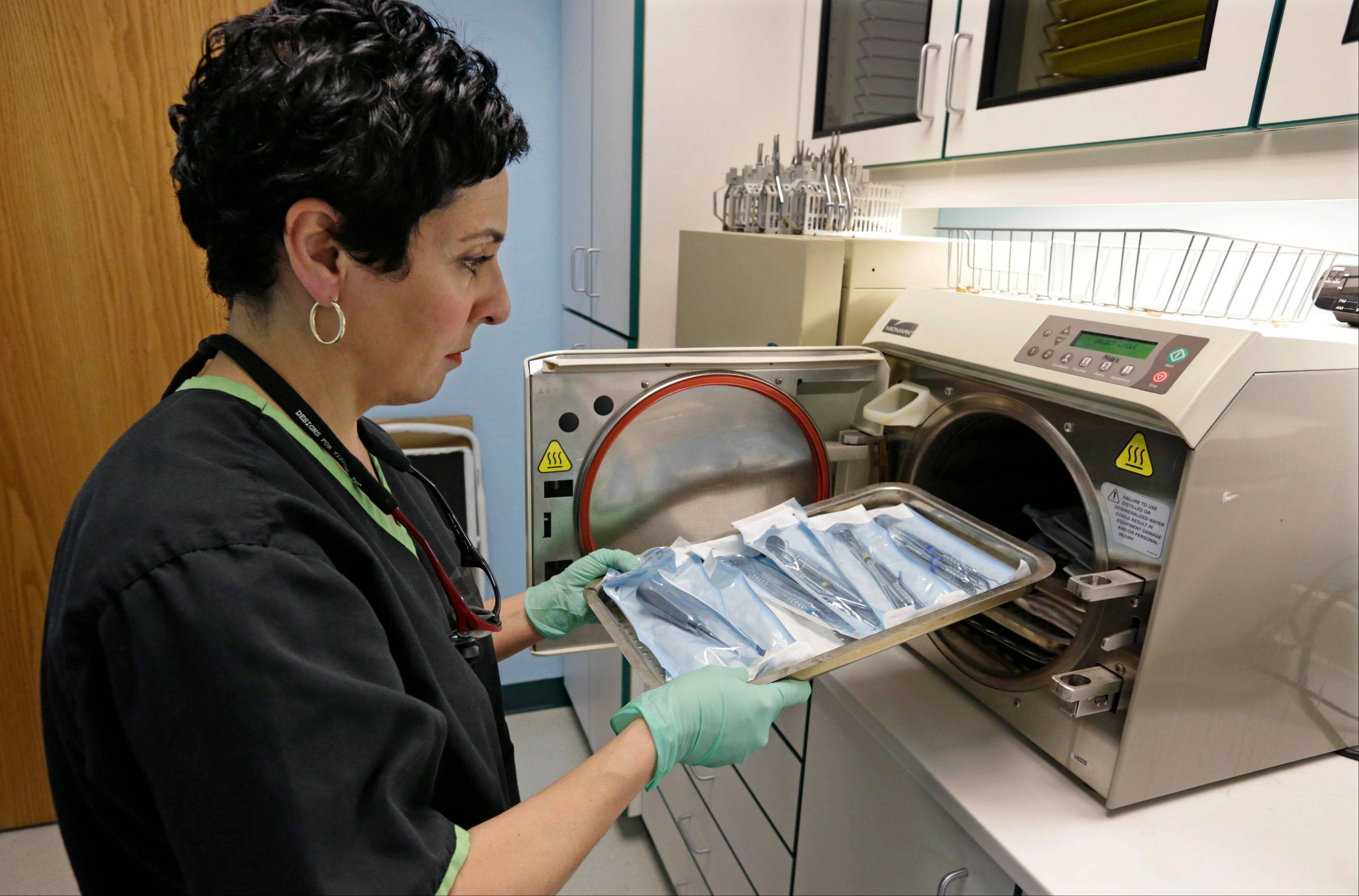 Dentist Alice G. Boghosian removes packages of properly sterilized dental instruments from an autoclave Friday that uses heat and steam to sterilize the tools, in Chicago. Health officials in Oklahoma are calling an oral surgeon there who used dirty equipment and risked cross-contamination a ìmenace to public healthî and are urging thousands of his patients to seek medical screenings for hepatitis B, hepatitis C and HIV.