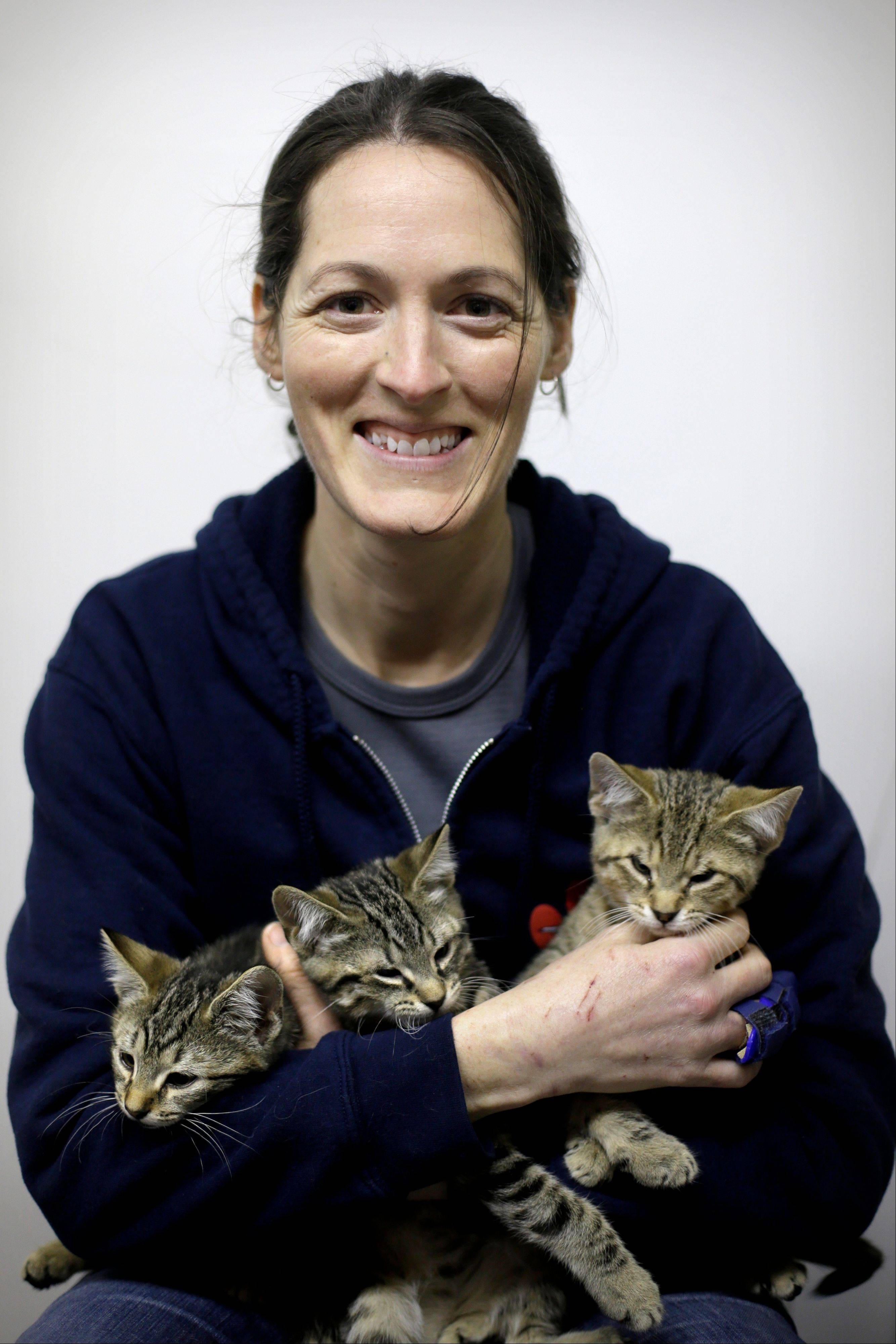 Red Paw founder Jen Leary cuddles kittens March 28 at their adoption facility in Philadelphia. The emergency relief service Red Paw has paired with the local Red Cross to care for animals displaced by flames, floods or other residential disasters, with the goal of eventually reuniting them with their owners.