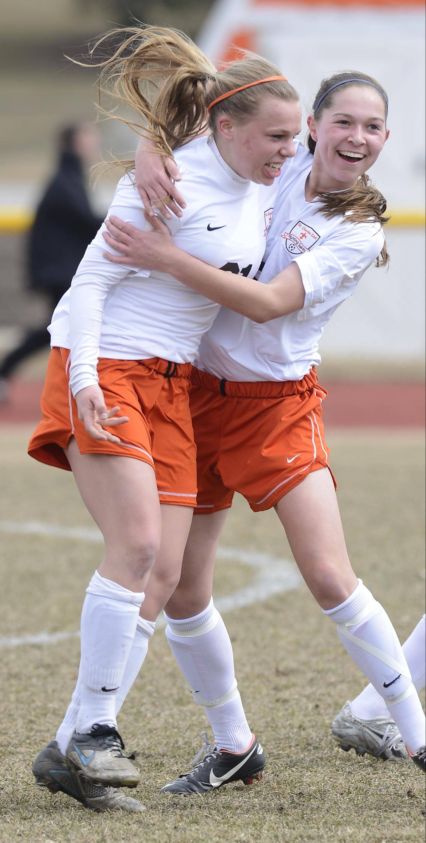 St. Charles East's Amanda Hilton, left, celebrates her goal with teammate Darcy Cunningham, after the Saints' third goal in just over three minutes of play against Batavia Saturday.