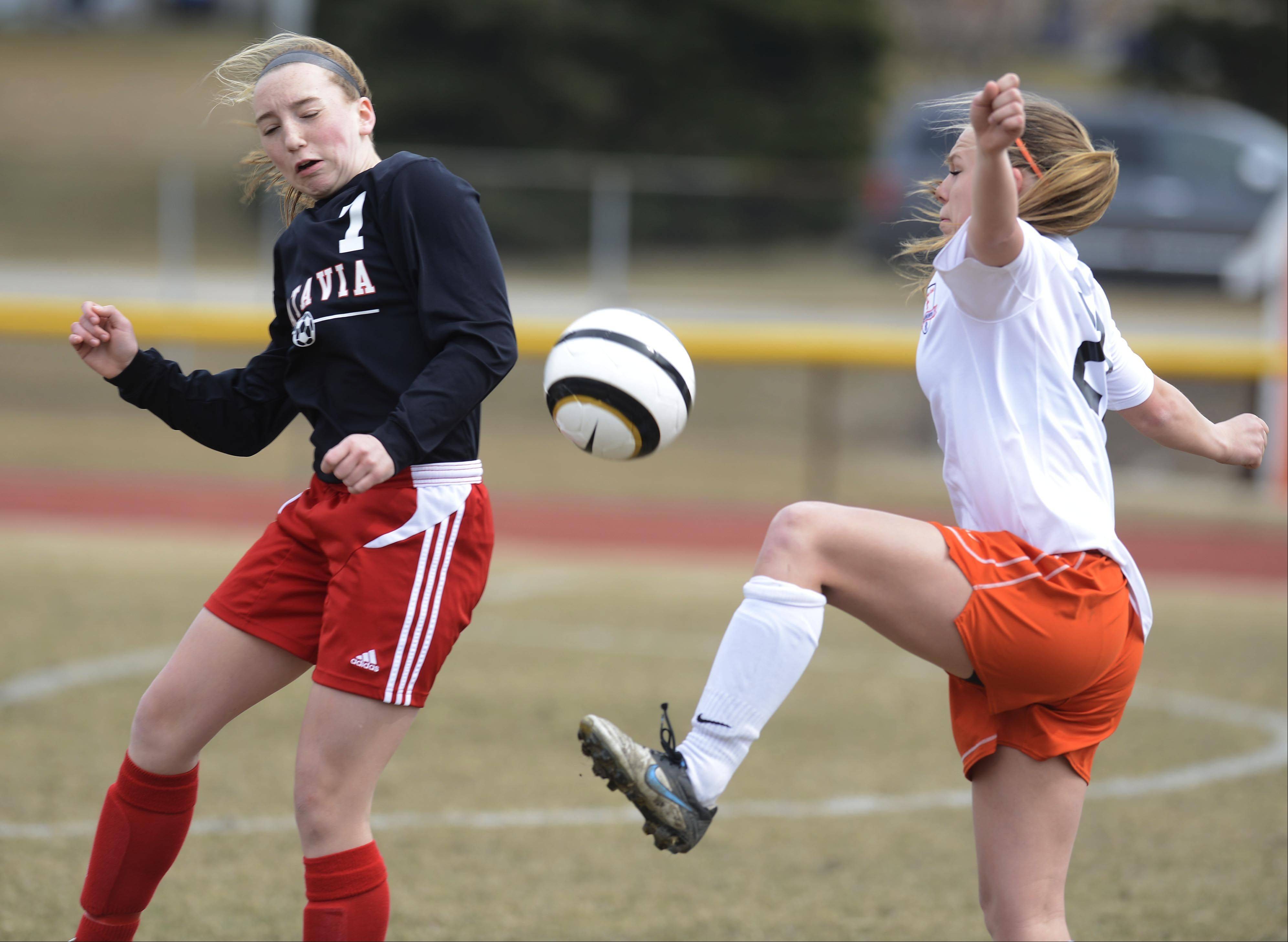 The ball gets between Batavia's Alexis Bryl, left, and St. Charles East's Amanda Hilton during Saturday's game.