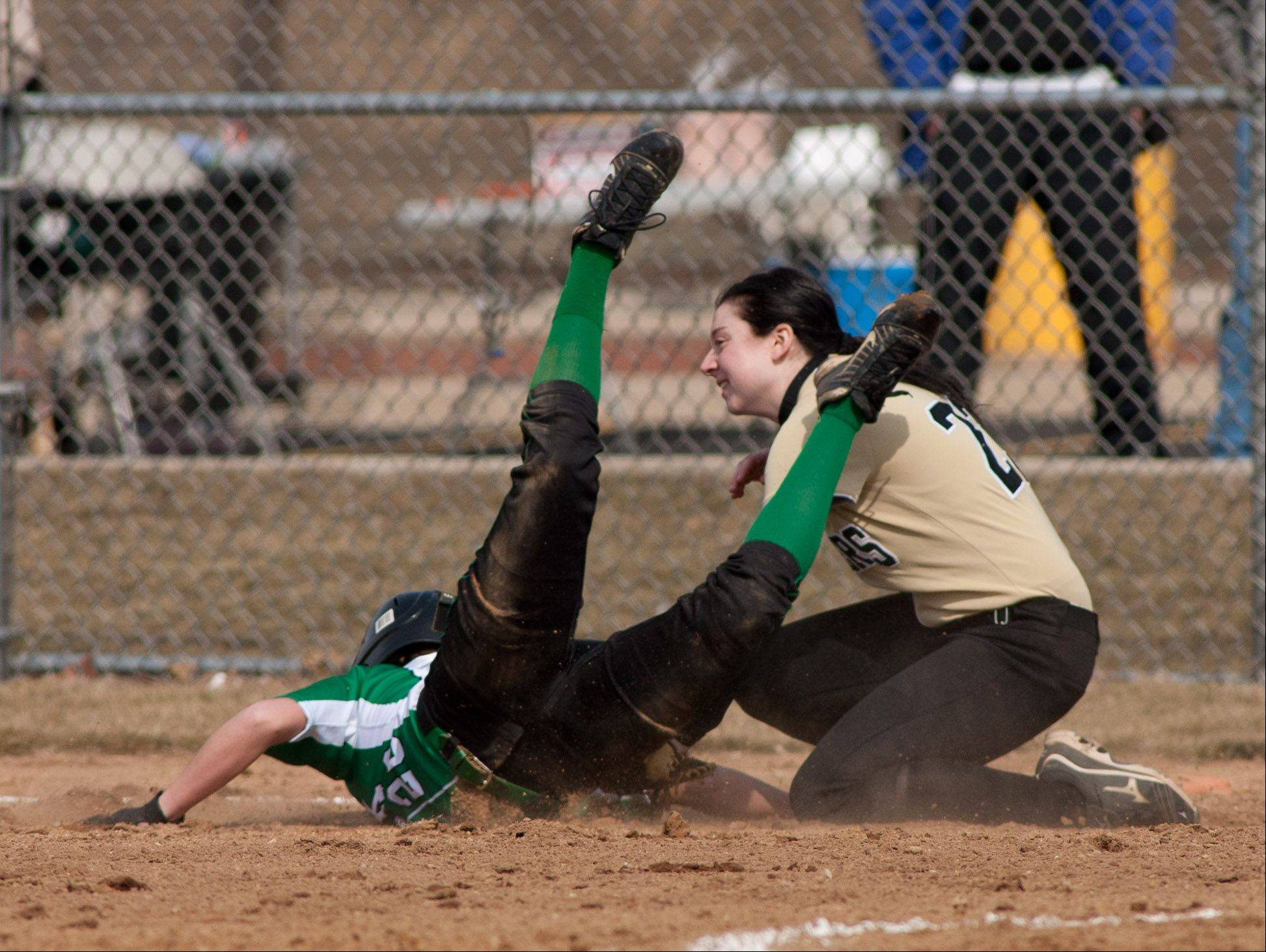 York's Gracie Sullivan slides safely back into first base, under the tag of Glenbard North's Heather Sperlazzo, during girls softball action.