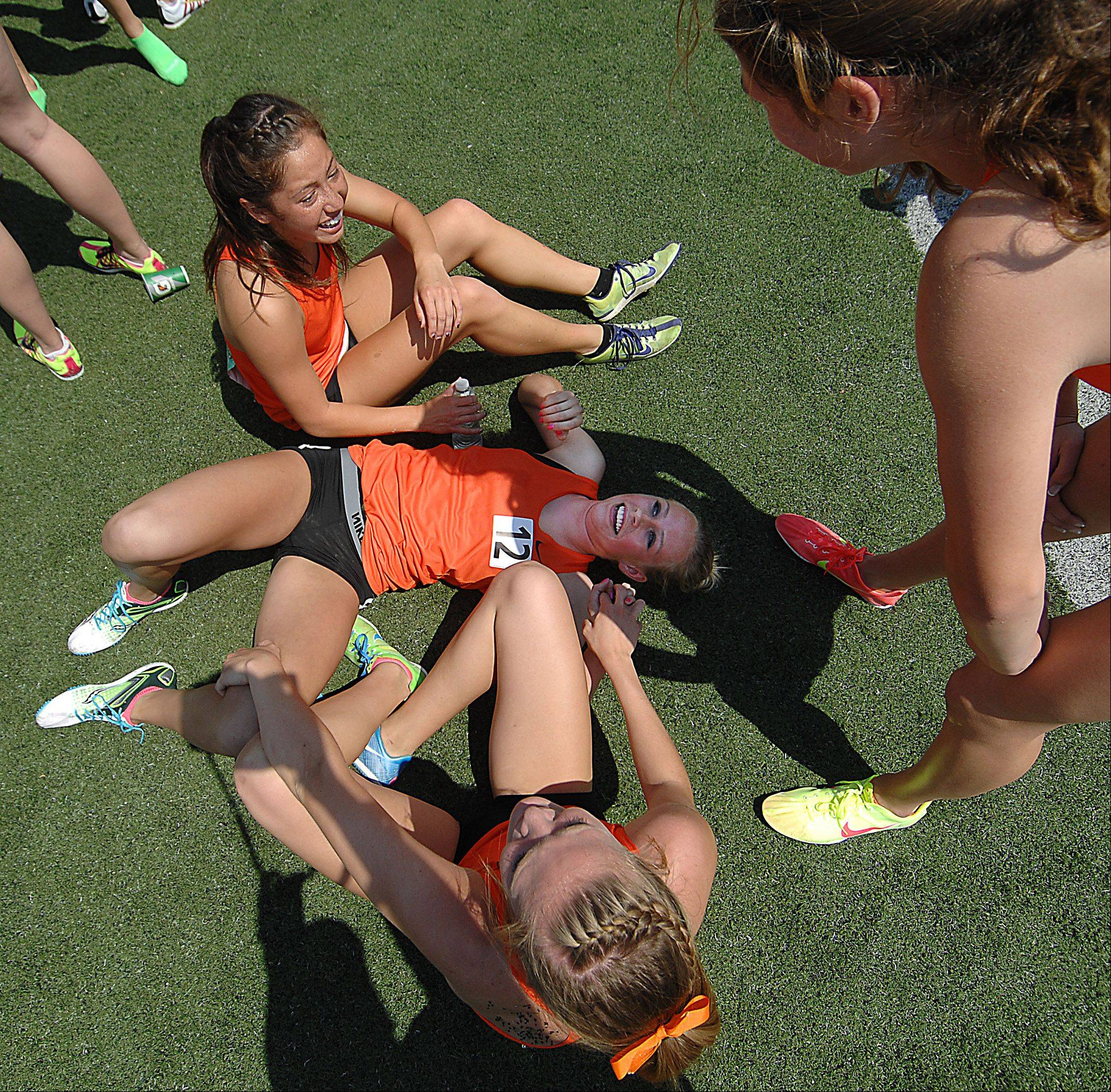 John Starks/jstarks@dailyherald.com ¬ Wheaton Warrenville South's McKenna Kiple lays on the ground as teammates Amy Yong, top, Hope Schmelzle, bottom, and Erin Hermann laugh with her after they set a meet record in the 3,200 meter relay Saturday at the Illinois High School Association girls state track and field finals at O'Brien Stadium at Eastern Illinois University in Charleston.