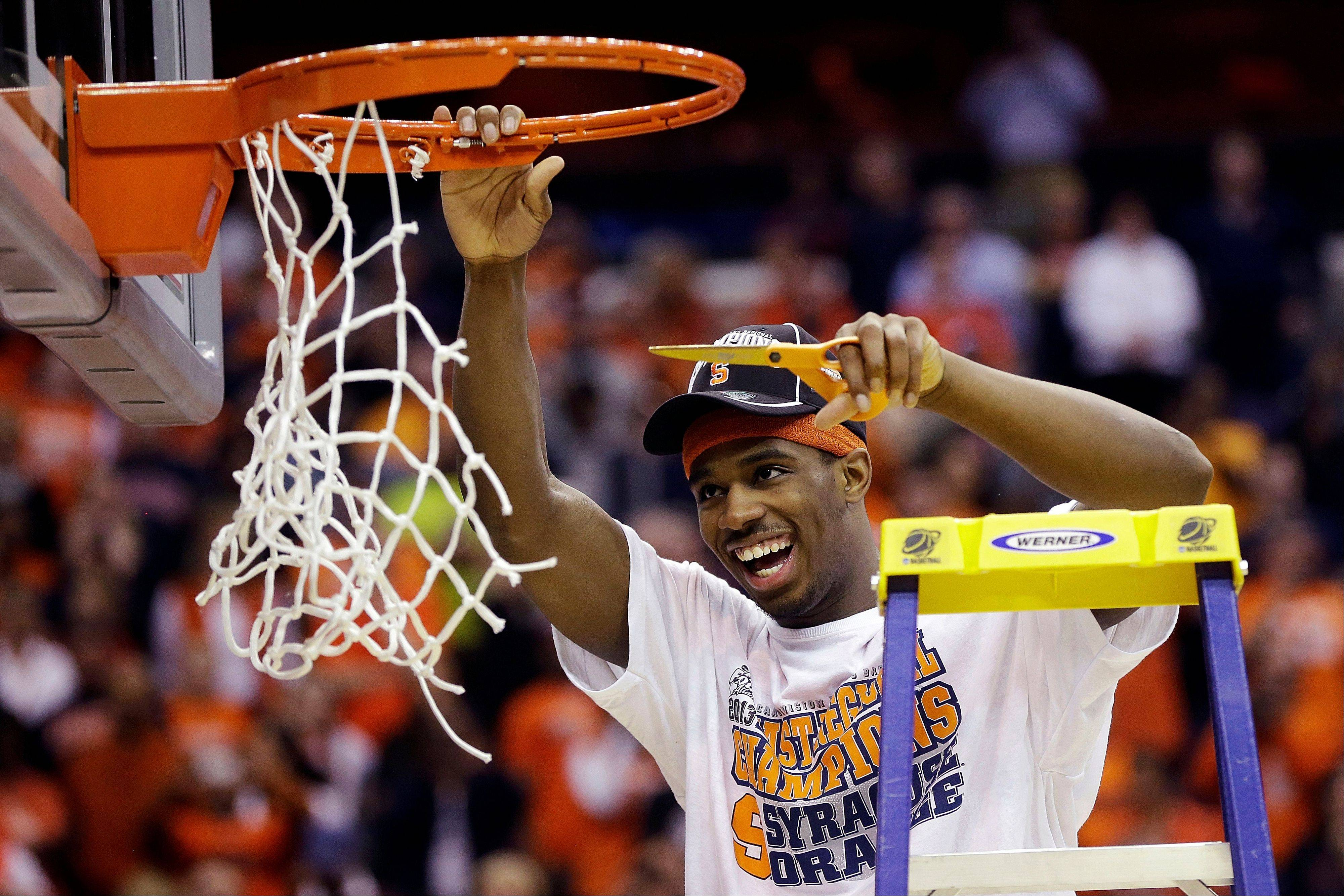 Syracuse forward C.J. Fair (5) cuts down the net following their 55-39 win over Marquette in the East Regional final in the NCAA men's college basketball tournament, Saturday, March 30, 2013, in Washington.