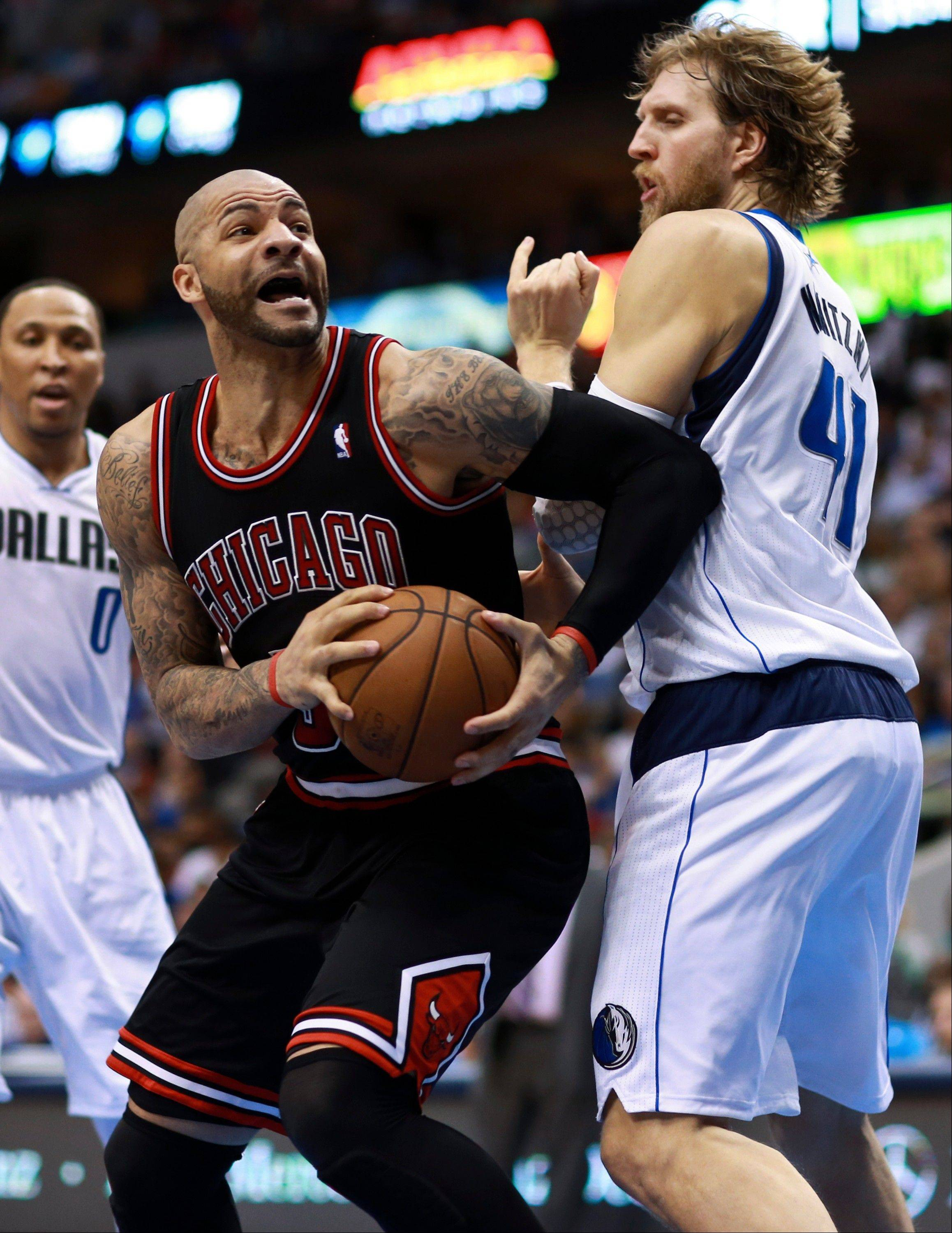 Chicago Bulls forward Carlos Boozer, center, is fouled by Dallas Mavericks forward Dirk Nowitzki (41), of Germany, under the net during the first half of an NBA basketball game, Saturday, March 30, 2013, in Dallas. Mavericks' Shawn Marion (0) is at left.