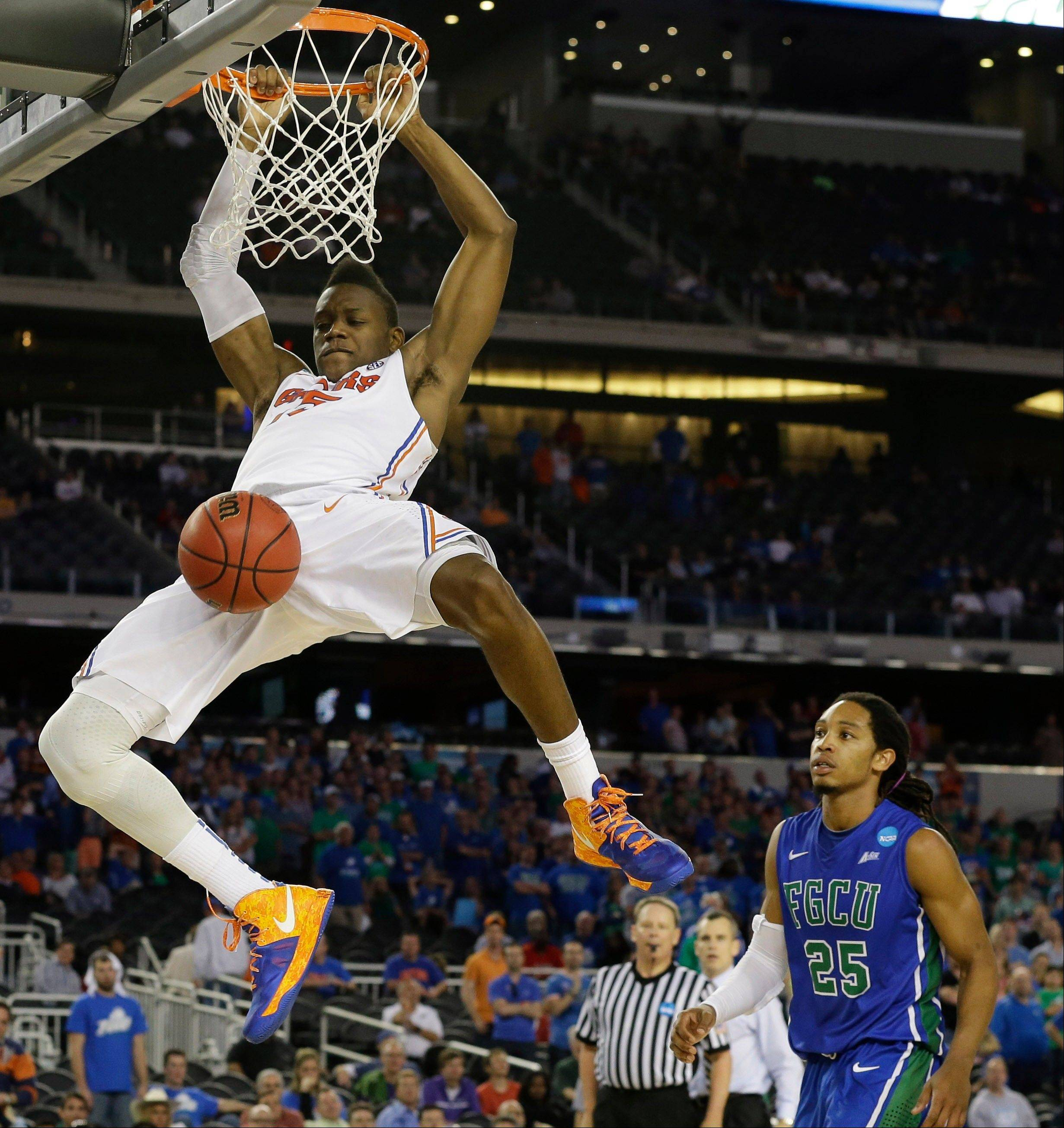Florida's Will Yeguete dunks against Florida Gulf Coast during the second half of a regional semifinal game in the NCAA college basketball tournament, Saturday, March 30, 2013, in Arlington, Texas.