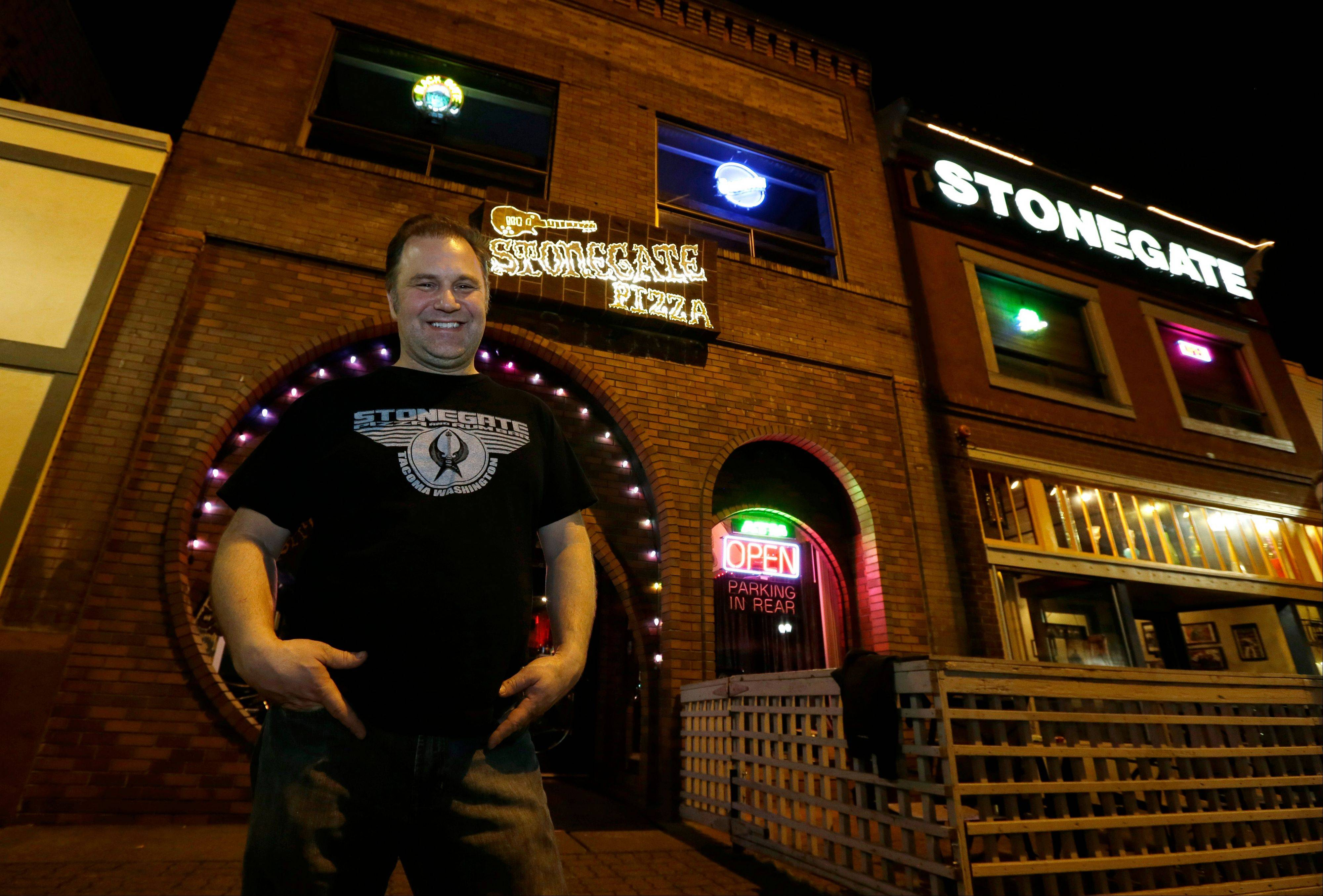 Jeff Call, owner of the Stonegate pizza-and-rum bar, poses for a photo in front of his business, Saturday, March 2, 2013, in Tacoma, Wash. Call charges patrons a small fee to become a member of the private second-floor club in the lounge area upstairs, which allows ìvaporizingî marijuana, a method that involves heating the marijuana without burning it. Last fall, Washington and Colorado became the first states to legalize marijuana use for adults over 21.