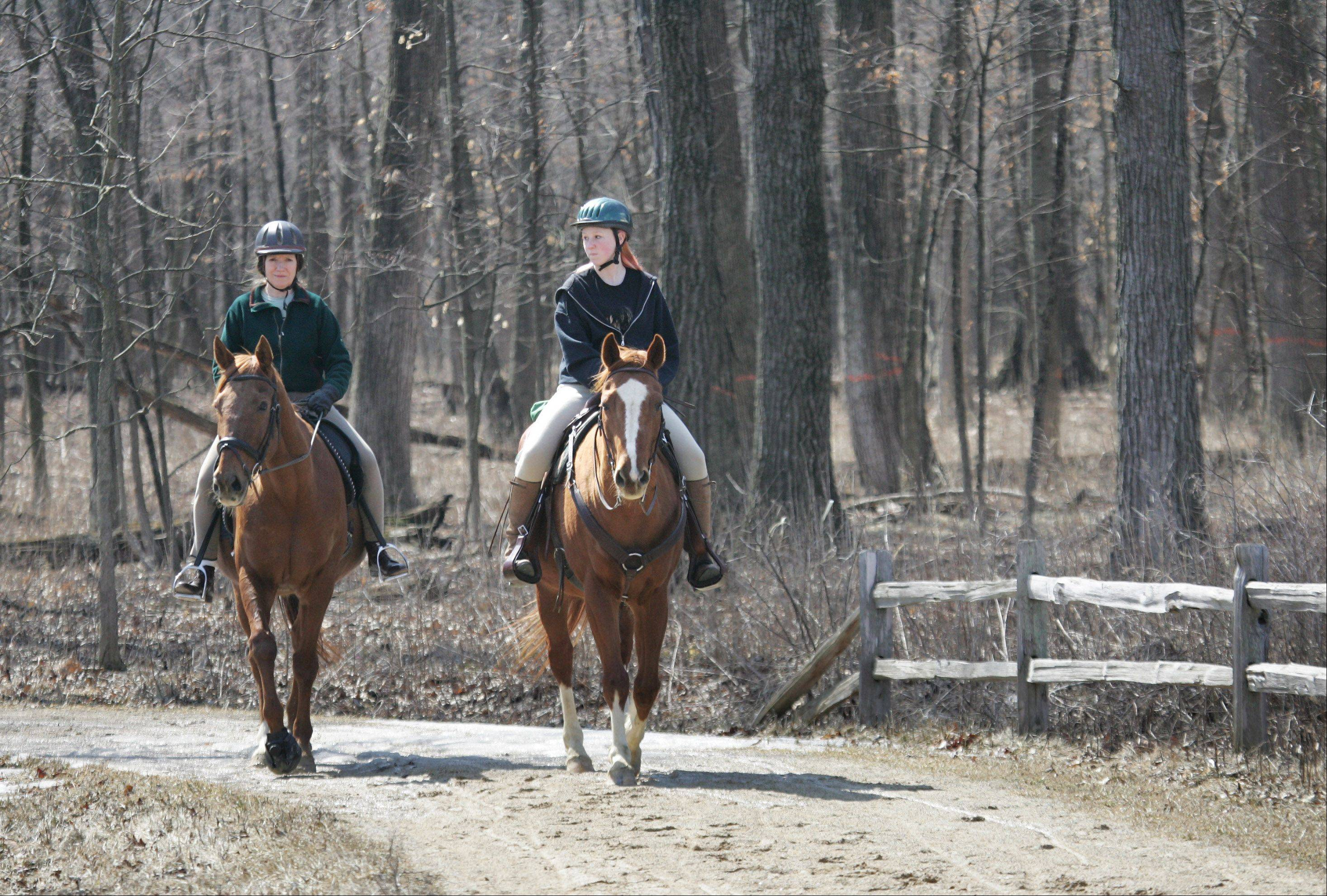 Sheridan Turner, of Glenview, left, rides Sir Winston and Emily Harrison, 15, of Hanover Park, rides Harley as they travel on the trails in MacArthur Woods near Vernon Hills on Easter Sunday. Area residents took advantage of the Lake County Forest Preserves on the nice spring day.