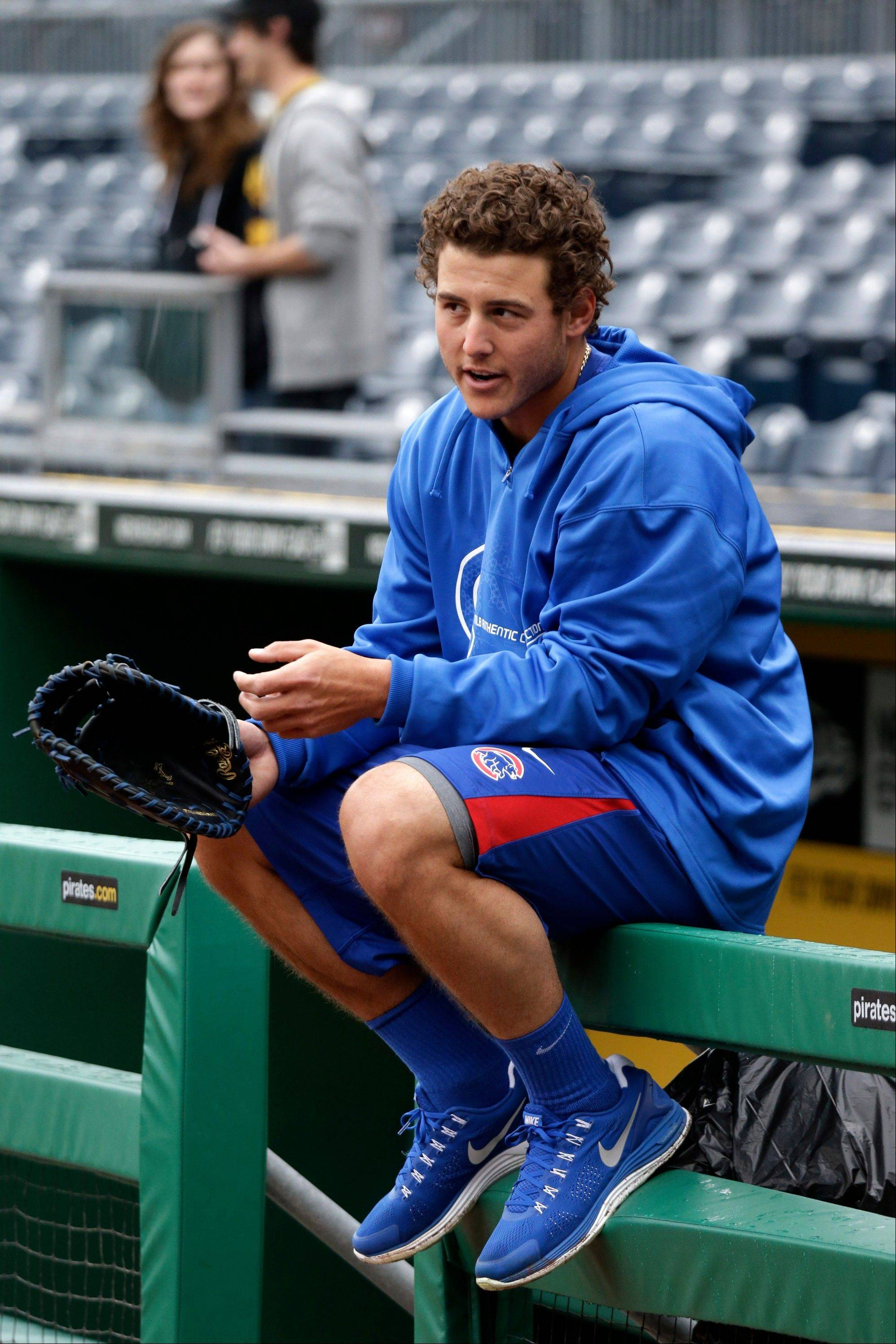 Cubs first baseman Anthony Rizzo sits on the dugout railing watching the Pittsburgh Pirates work out at PNC Park in Pittsburgh on Sunday. The two teams open their seasons Monday.