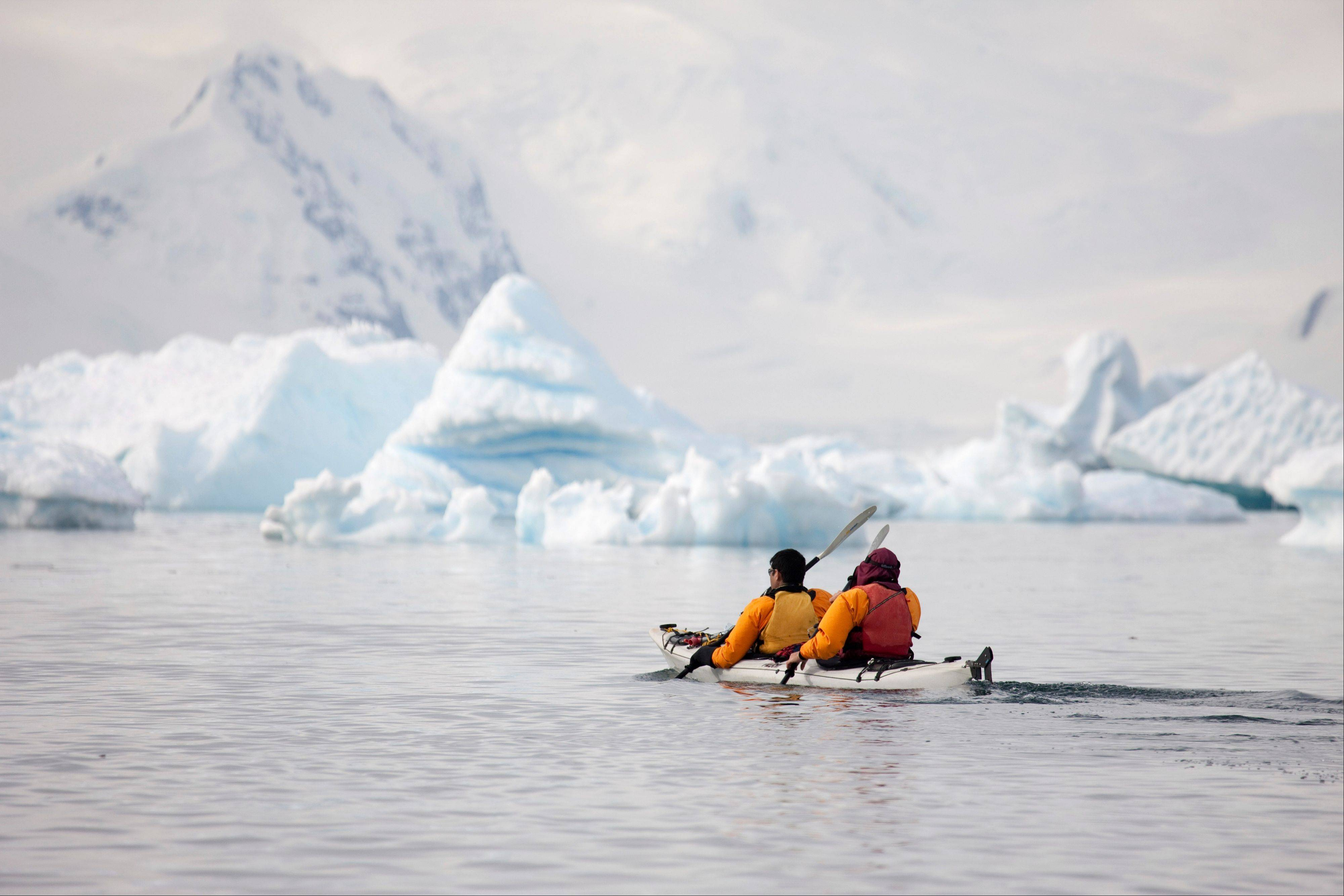 Tourists paddle their kayak along the Antarctic Peninsula.