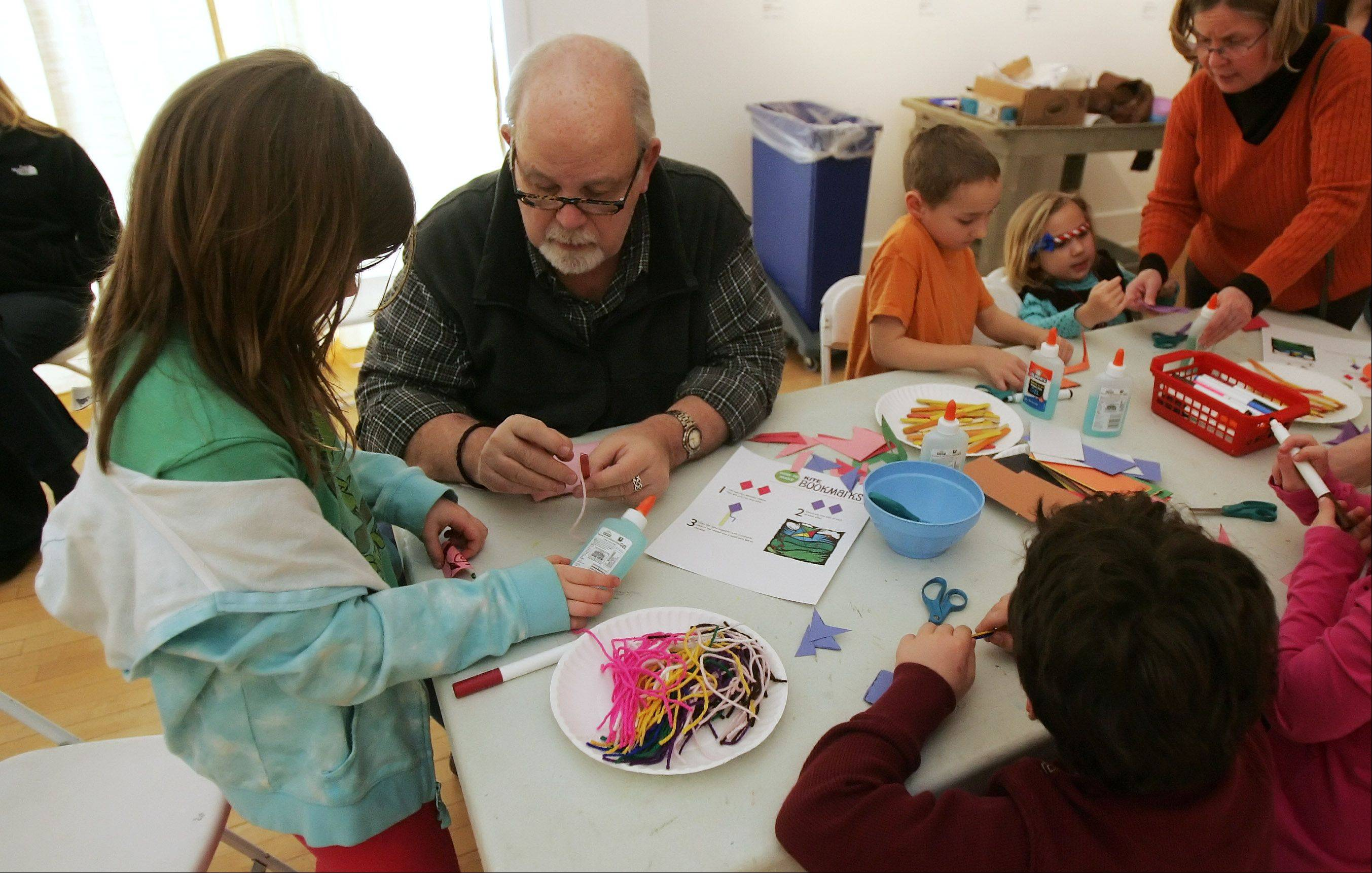 "Volunteer Mike Downey helps Heloise Jacobs, 8, both of Buffalo Grove, make a kite bookmark during the ""Spring Break Fun"" program Tuesday at the Lake County Discovery Museum near Wauconda. Kids worked on crafts including sack puppets, kite bookmarks and paper daffodils."
