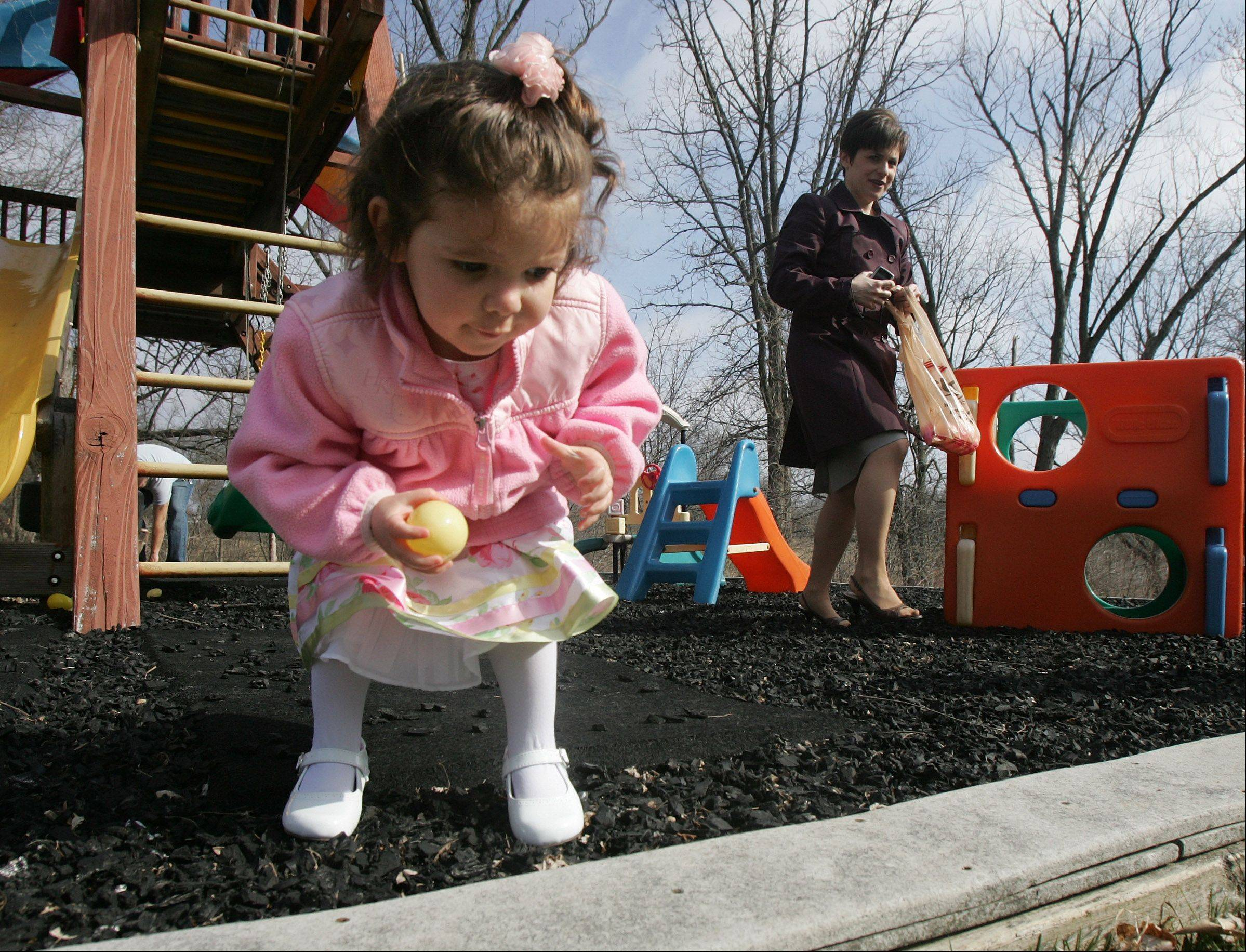 Two-year-old Corinne Drucker, of Hawthorn Woods, collects eggs as her mother, Jeanene, watches during the Easter egg hunt at Long Grove Community Church on Easter Sunday. Children collected eggs in different age categories looking for golden eggs and prizes.