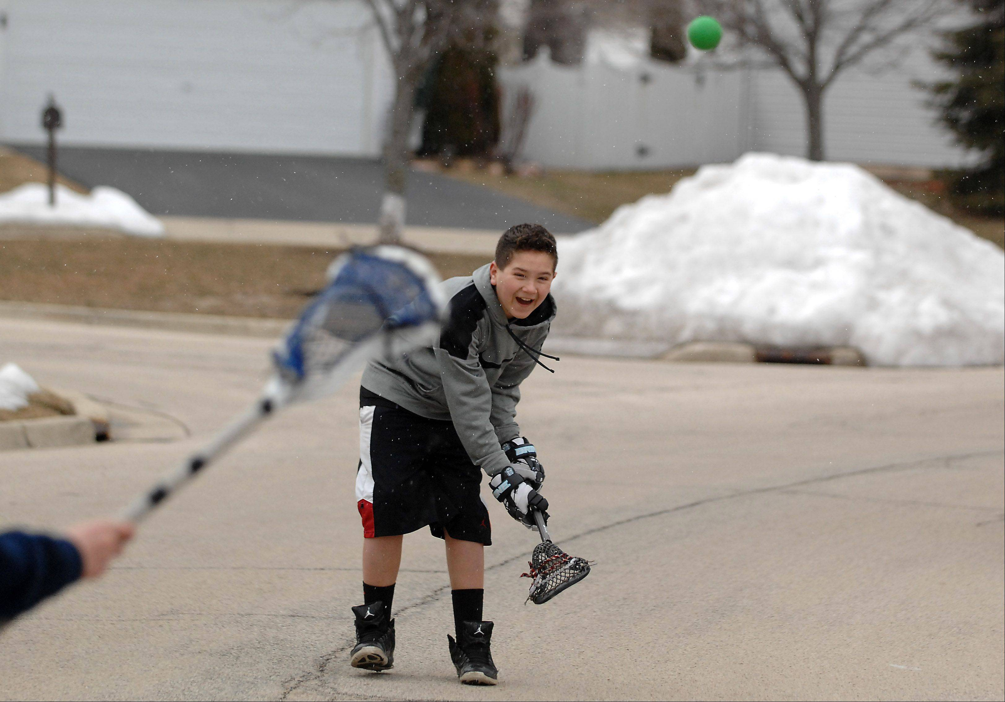 "Nathan Carrillo, 13, throws the ball to Connor McGuffin, 14, as they play lacrosse in the street in their South Elgin neighborhood on their first day of spring break from Kenyon Woods Middle School Monday. ""This the coldest I've ever been on spring break,"" said the shorts-clad Carrillo. The kids both play for Mid-Valley Lacrosse and weren't going to let a little cold and snow stop them from practicing."