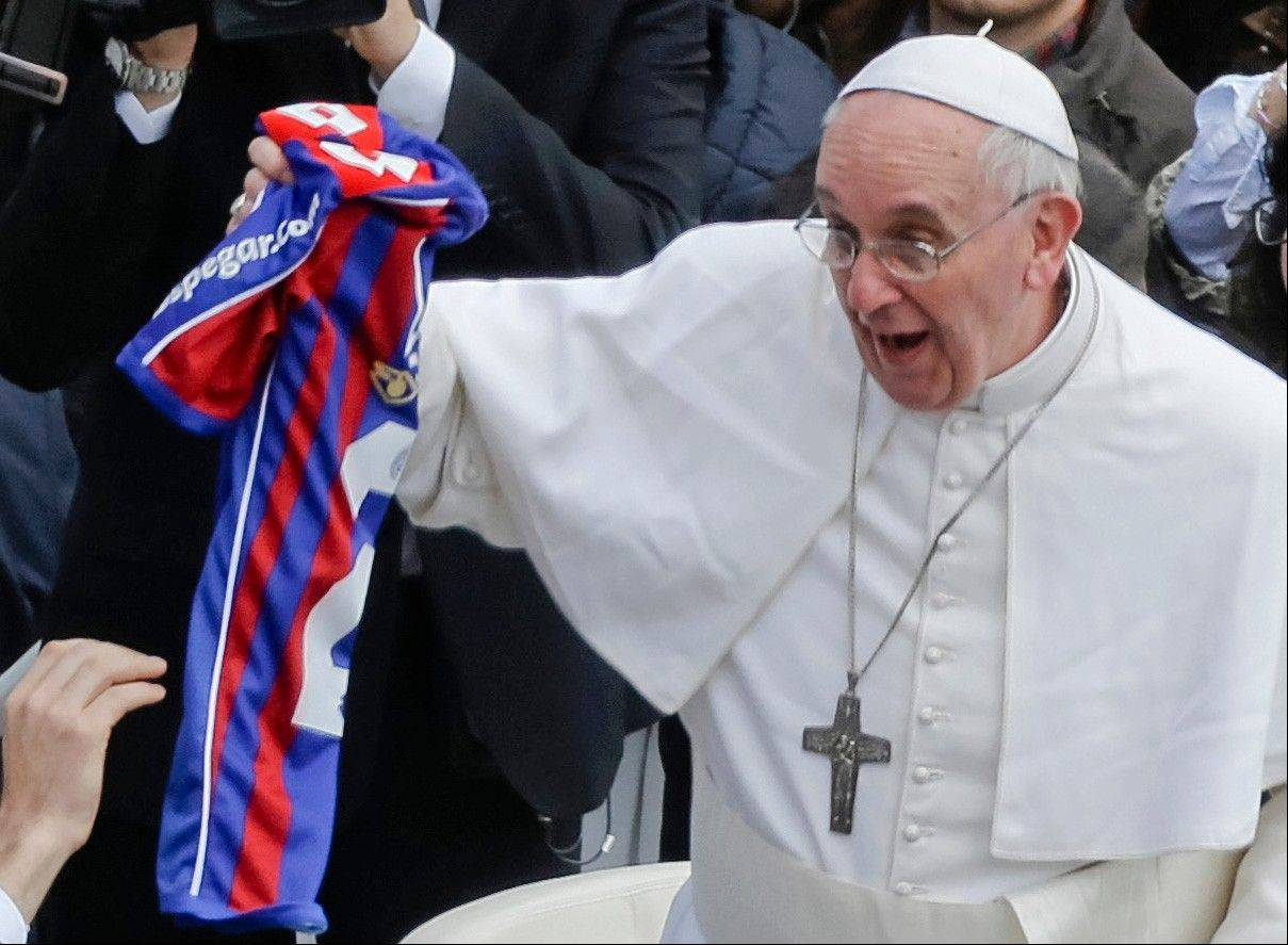 Pope Francis holds a San Lorenzo's jersey, the Buenos Aires soccer team, handed to him by a faithful at the end of the Easter mass in St. Peter's Square at the Vatican Sunday.