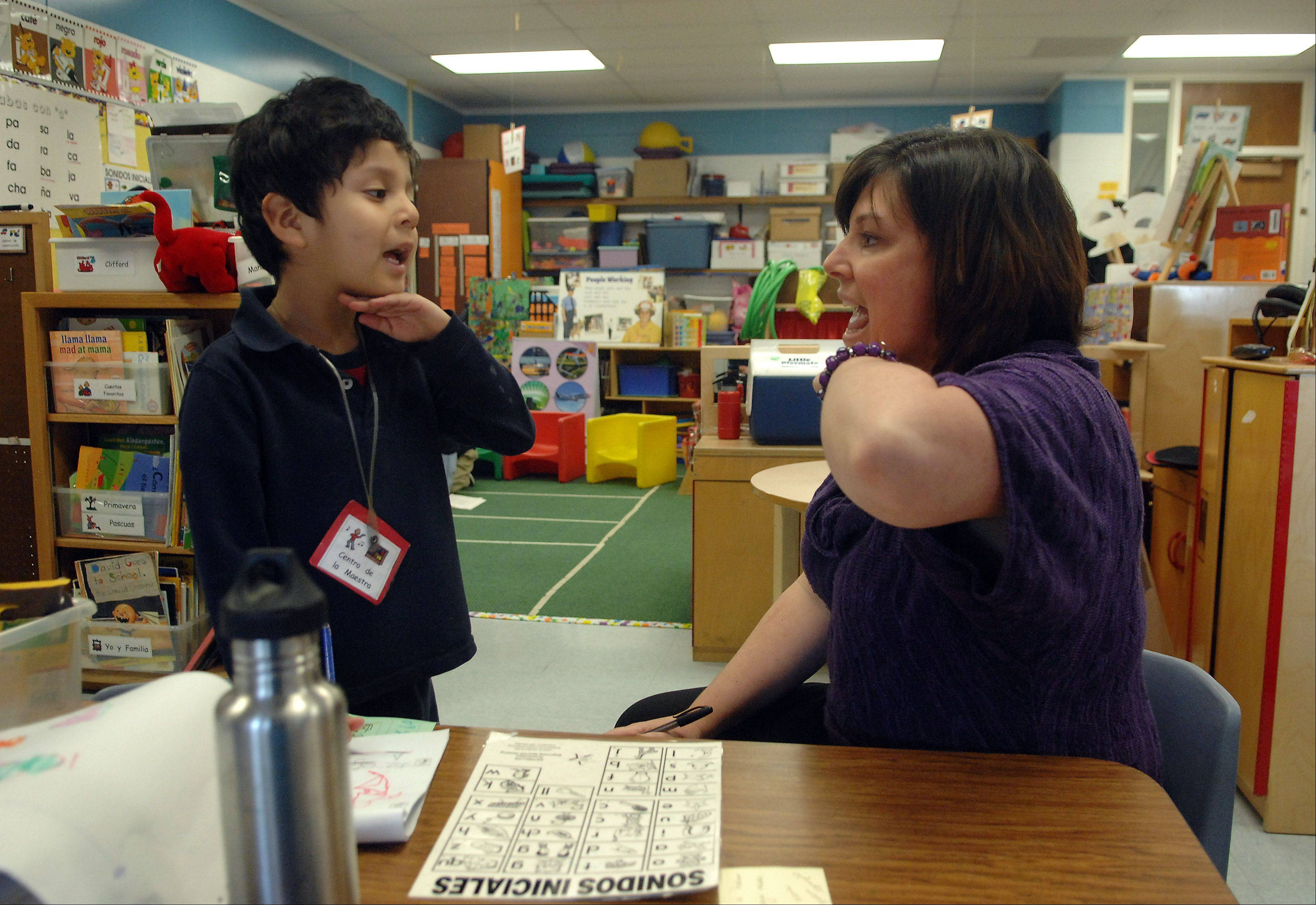 Garfield Elementary School kindergarten teacher Angie Gallegos works with JoShoa Olvera on his English pronunciation. Gallegos constantly documents classroom behavior as part of a new assessment of kindergartners on their school readiness.