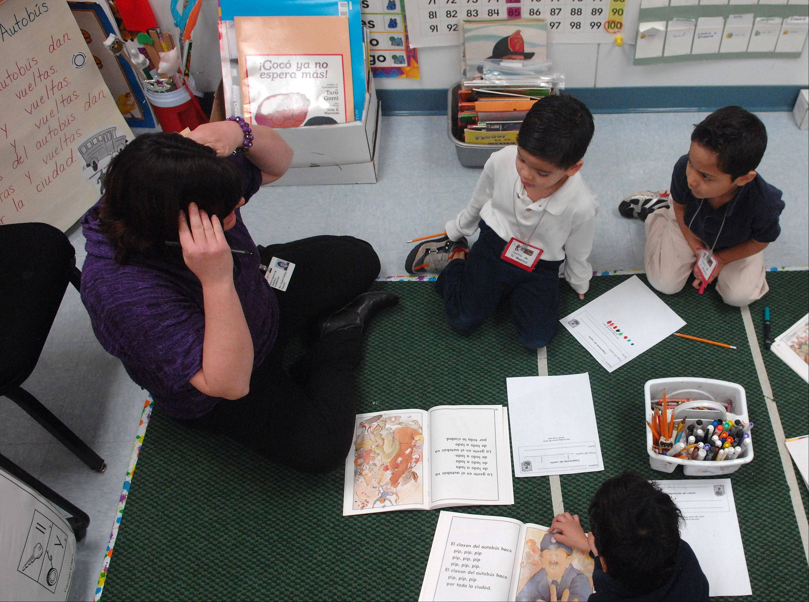 Garfield Elementary School kindergarten teacher Angie Gallegos works with students during a dual language, full-day kindergarten class. Gallegos is constantly using classroom observations to complete a new assessment of kindergartners on their school readiness.