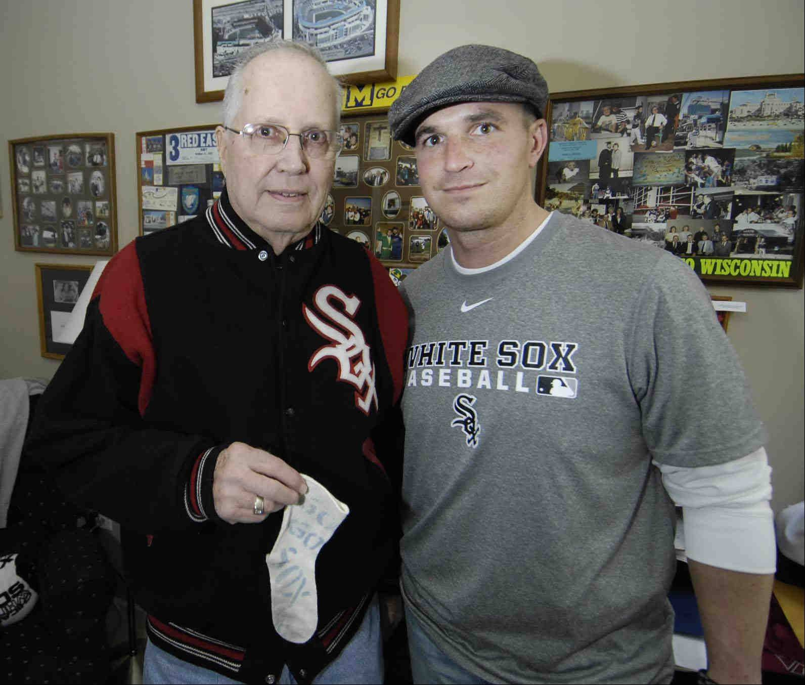 "Frank Gambro of Elgin will be going to his 60th consecutive White Sox home opener. He holds a ""Go Go Sox"" sock that was pinned on his first son Fran's crib as a baby. He poses with Fran's son, Adam."
