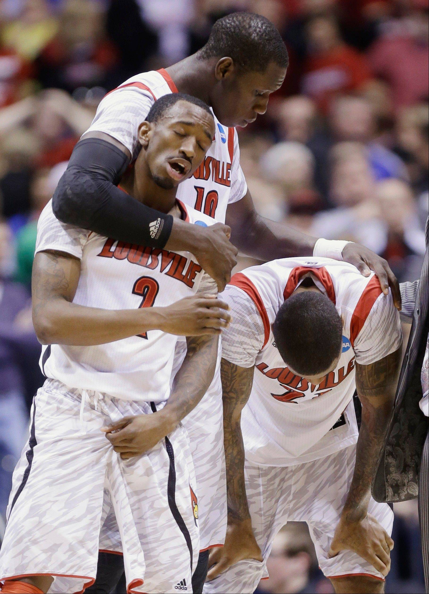 Louisville's Russ Smith (2), Gorgui Dieng (10) and Chane Behanan react to guard Kevin Ware's injury during the first half of the Midwest Regional final against Duke in the NCAA college basketball tournament, Sunday, March 31, 2013, in Indianapolis.