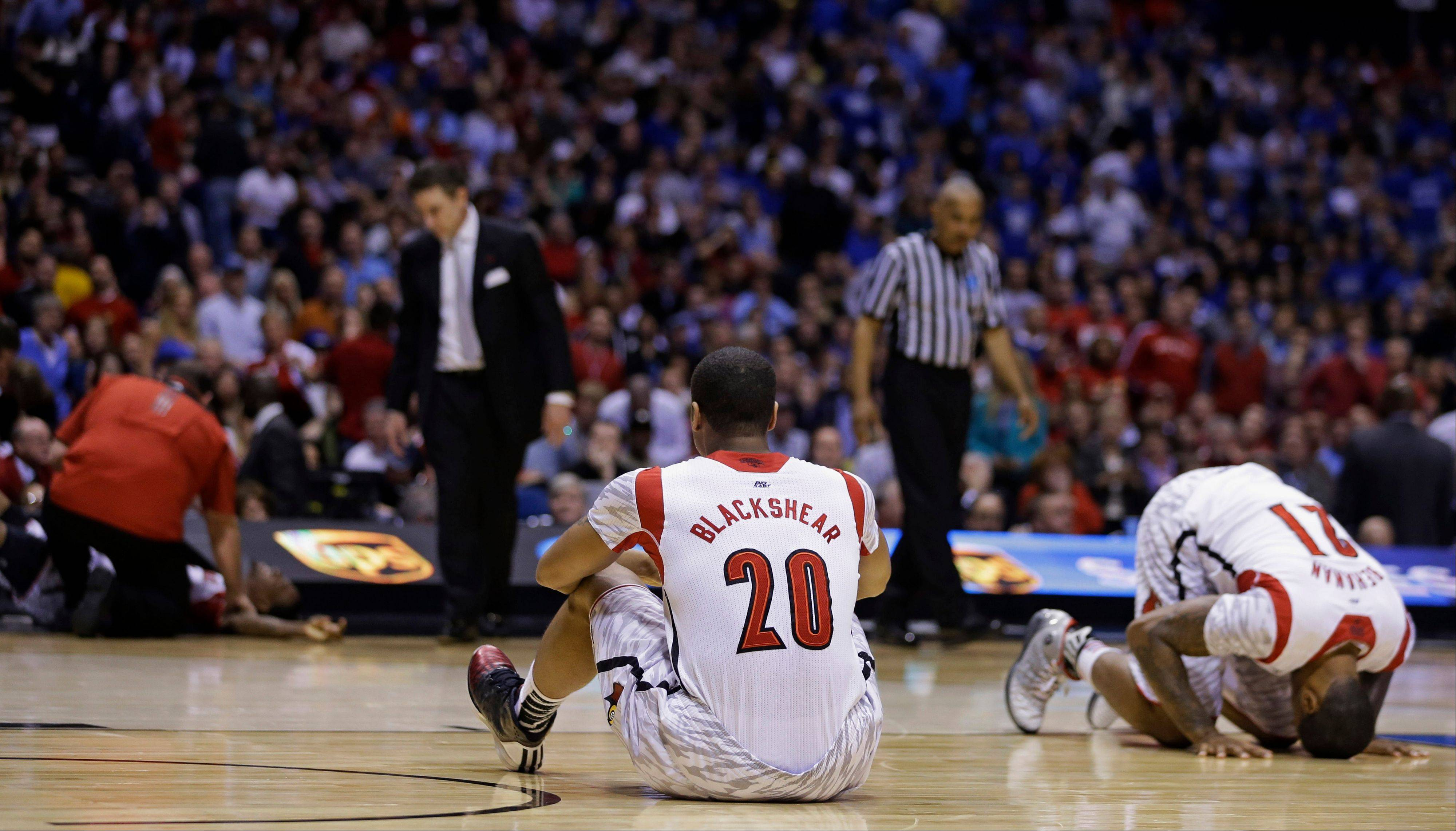 Louisville's Wayne Blackshear (20) and Chane Behanan (21) react to Kevin Ware's injury during the first half of the Midwest Regional final in the NCAA college basketball tournament, Sunday, March 31, 2013, in Indianapolis.