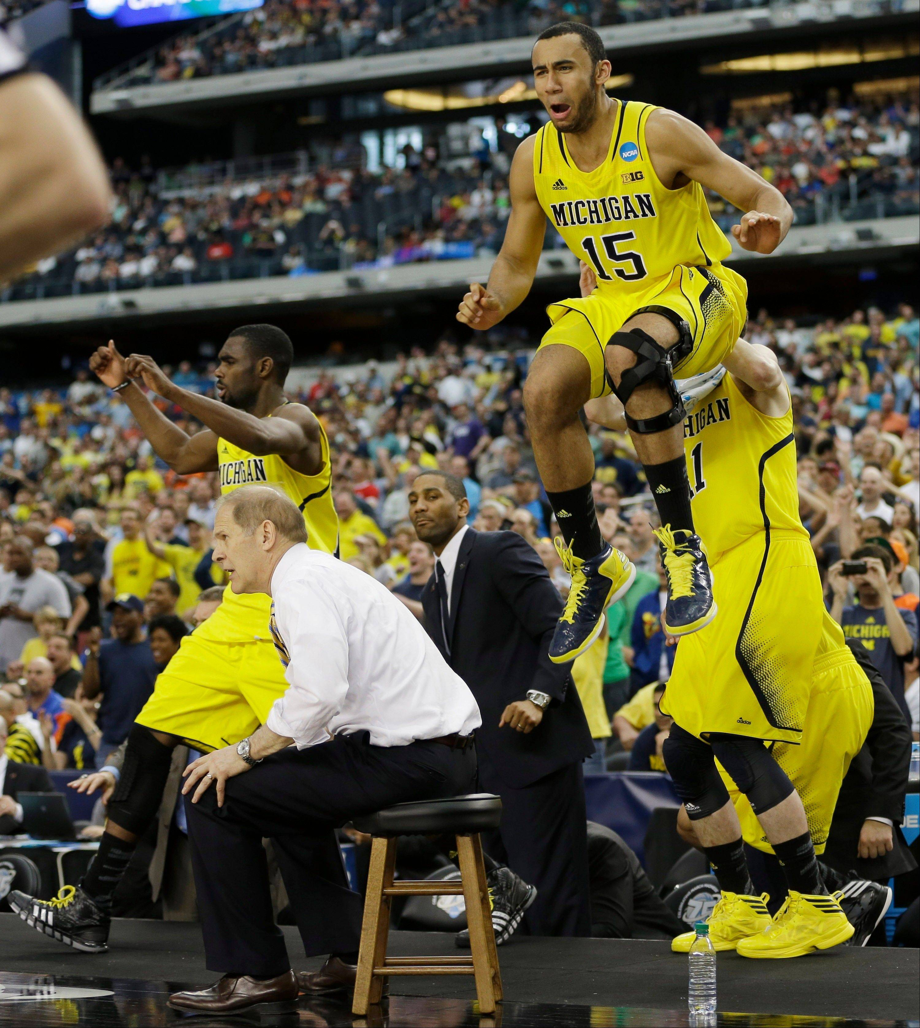 Michigan head coach John Beilein and players including Jon Horford (15) react against Florida during the second half of a regional final game in the NCAA college basketball tournament, Sunday, March 31, 2013, in Arlington, Texas. Michigan won 79-59.