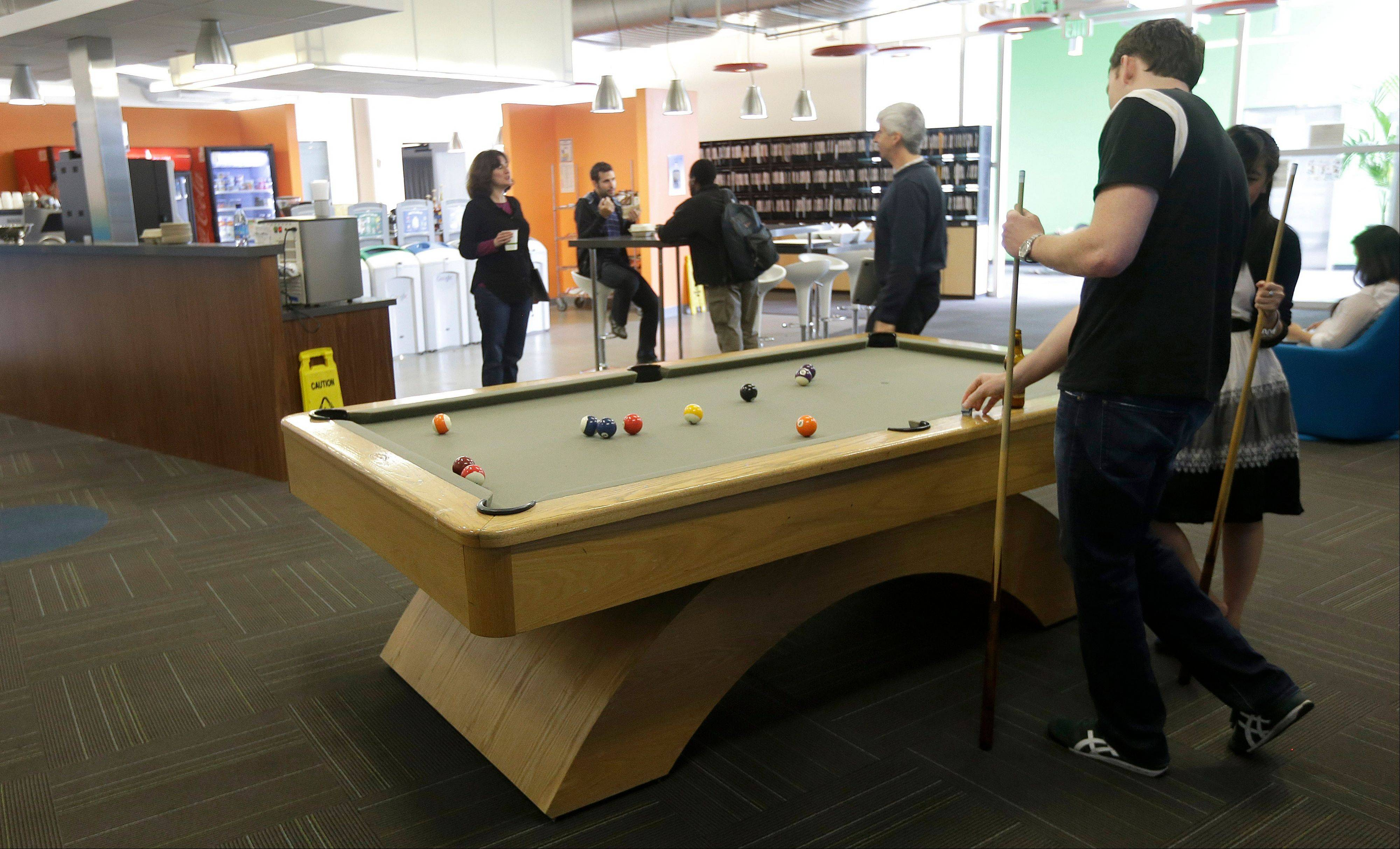 Google employees shoot pool at in a break room at the Google campus in Mountain View, Calif..