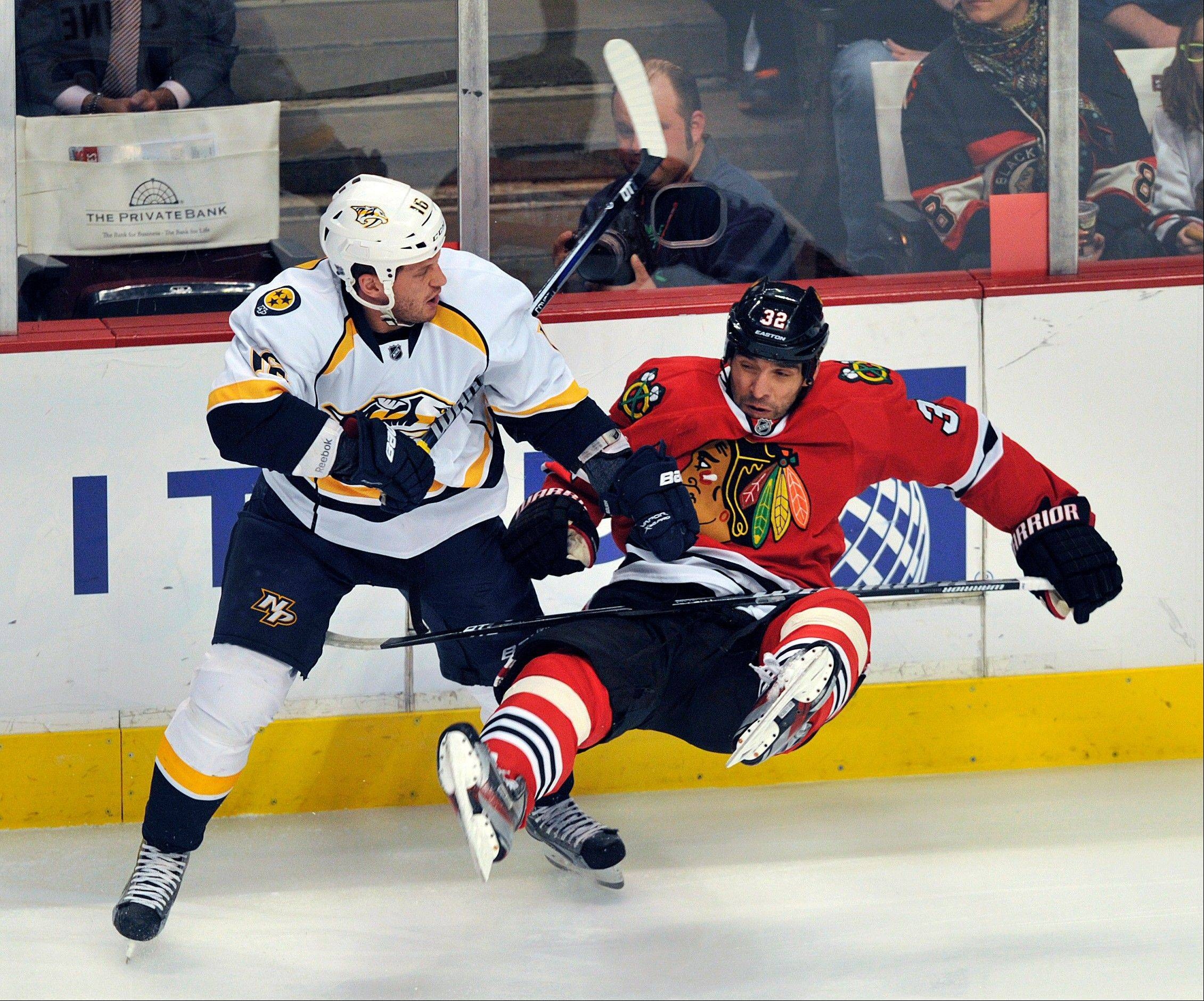 Nashville Predators' Richard Clune left, checks the Chicago Blackhawks' Michal Rozsival during the first period of an NHL hockey game Monday, April 1, 2013, in Chicago.