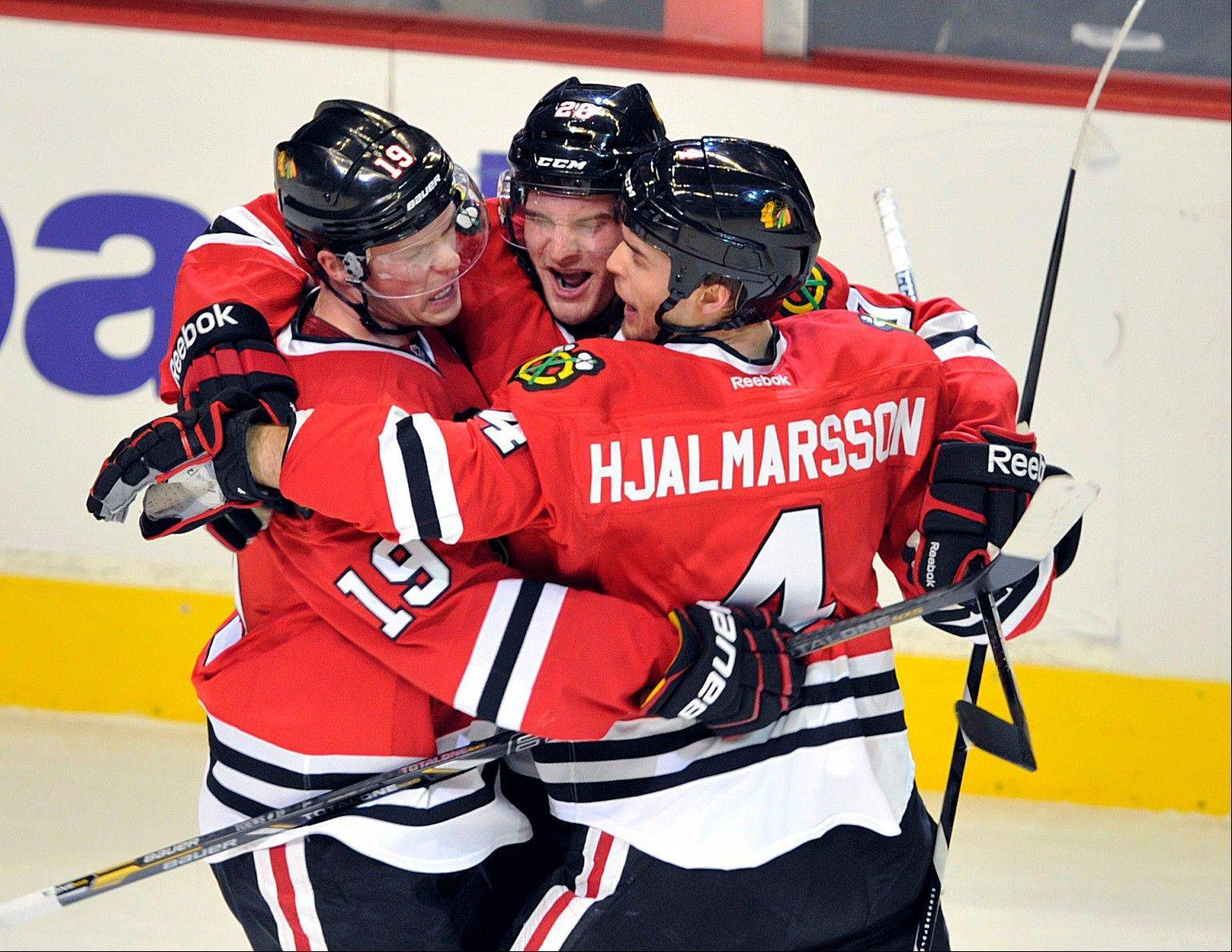 Chicago Blackhawks' Brandon Saad, center, celebrates with teammates Jonathan Toews (19) and Niklas Hjalmarsson (4) after Saad's goal against the Nashville Predators during the first period.