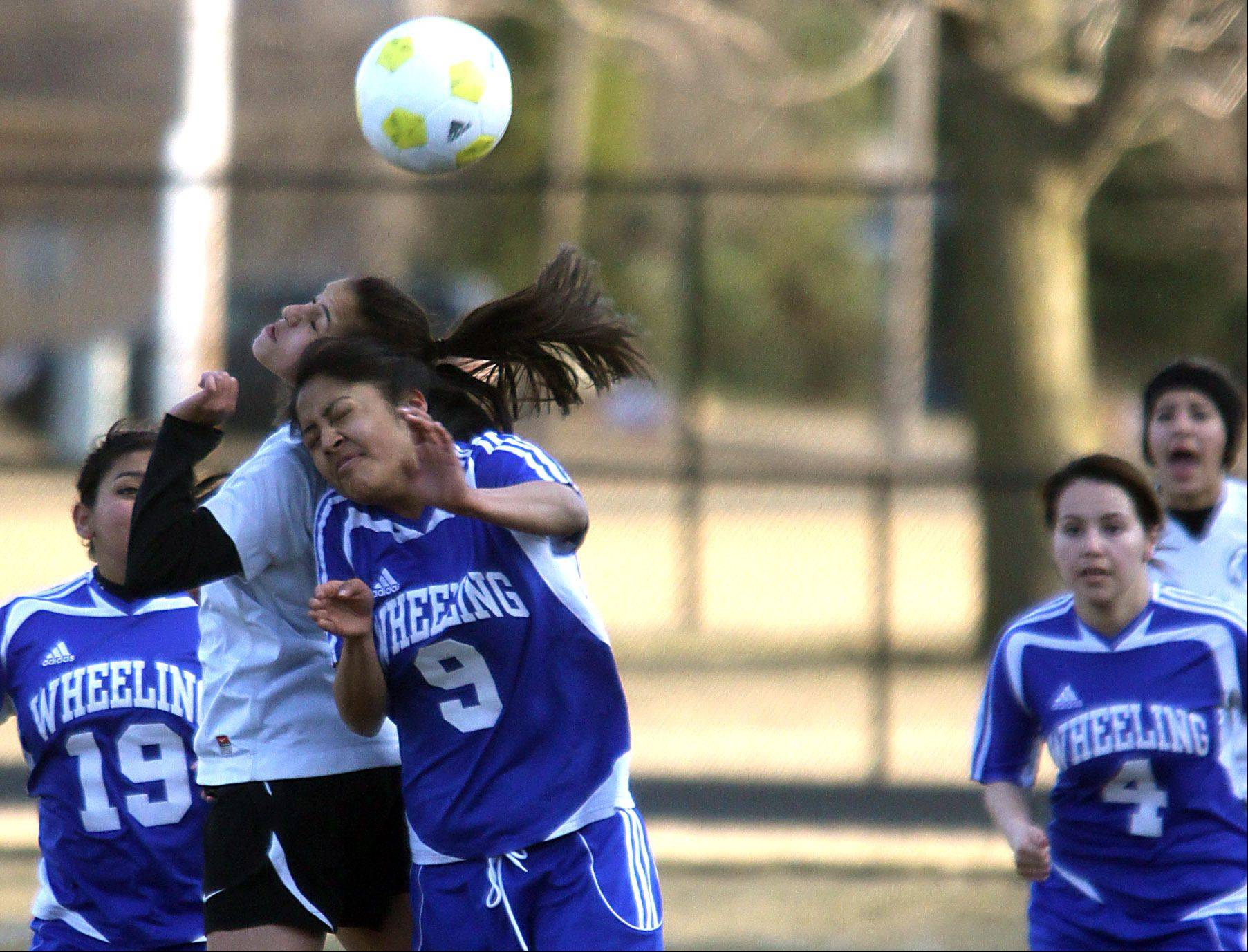 Wheeling's Cindy Castillo, front, battles Maine West's Joanne Stanfa for a header during action at Maine West on Monday.