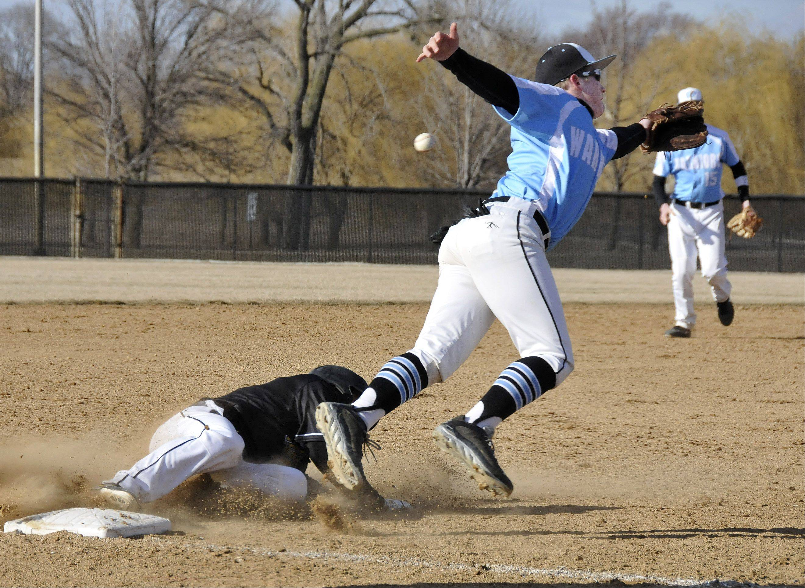 Willowbrook's third baseman Jake Cady lunges for a throw from their catcher as Hinsdale South's Don Buonavolanto slides into third. After the ball sailed into left field, he subsequently scored on the play. Hinsdale South played baseball Monday afternoon at Willowbrook High School in Villa Park.