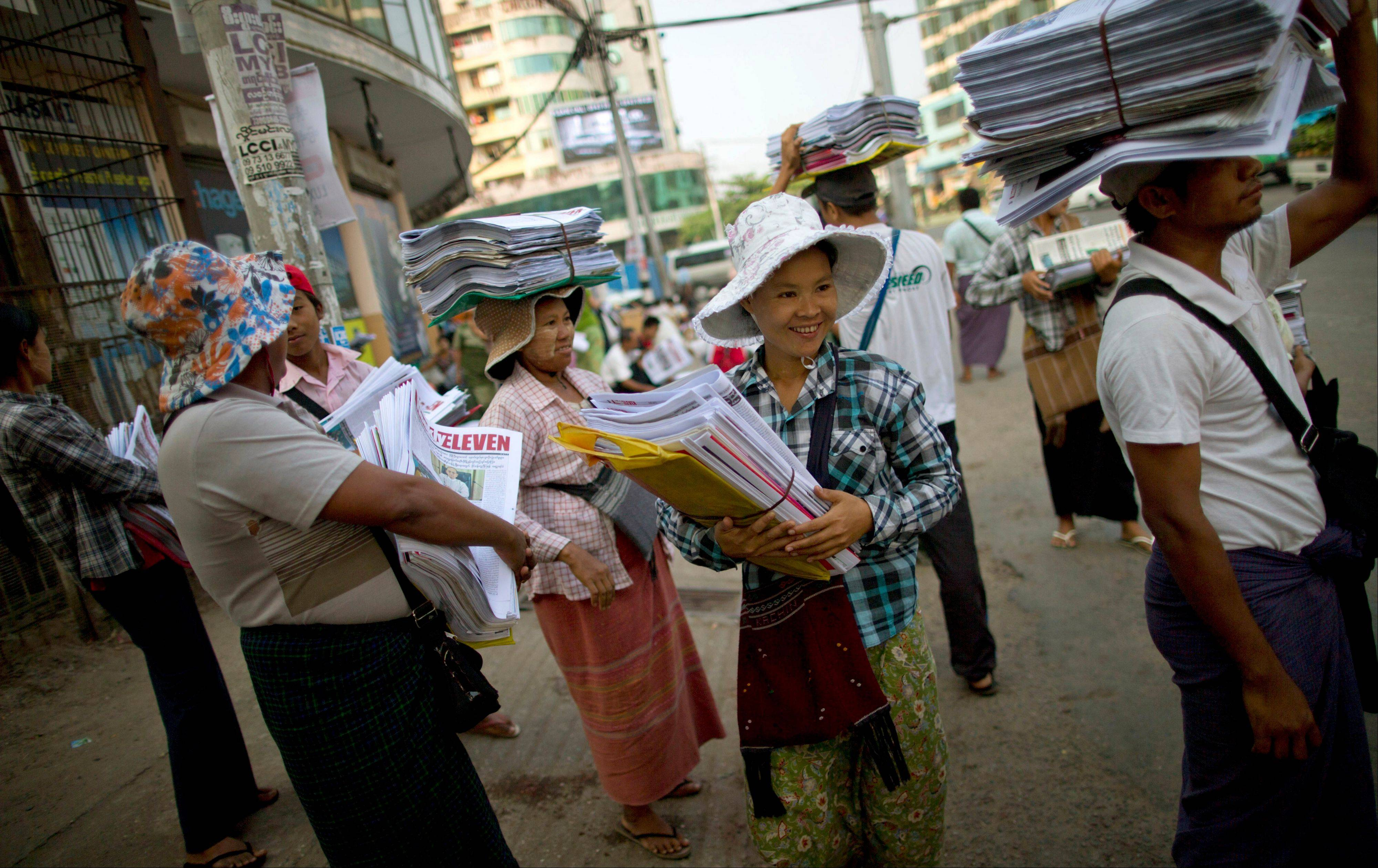 Newspaper sellers wait for a bus after receiving newspapers from a wholesale dispatcher in Yangon, Myanmar, Monday.