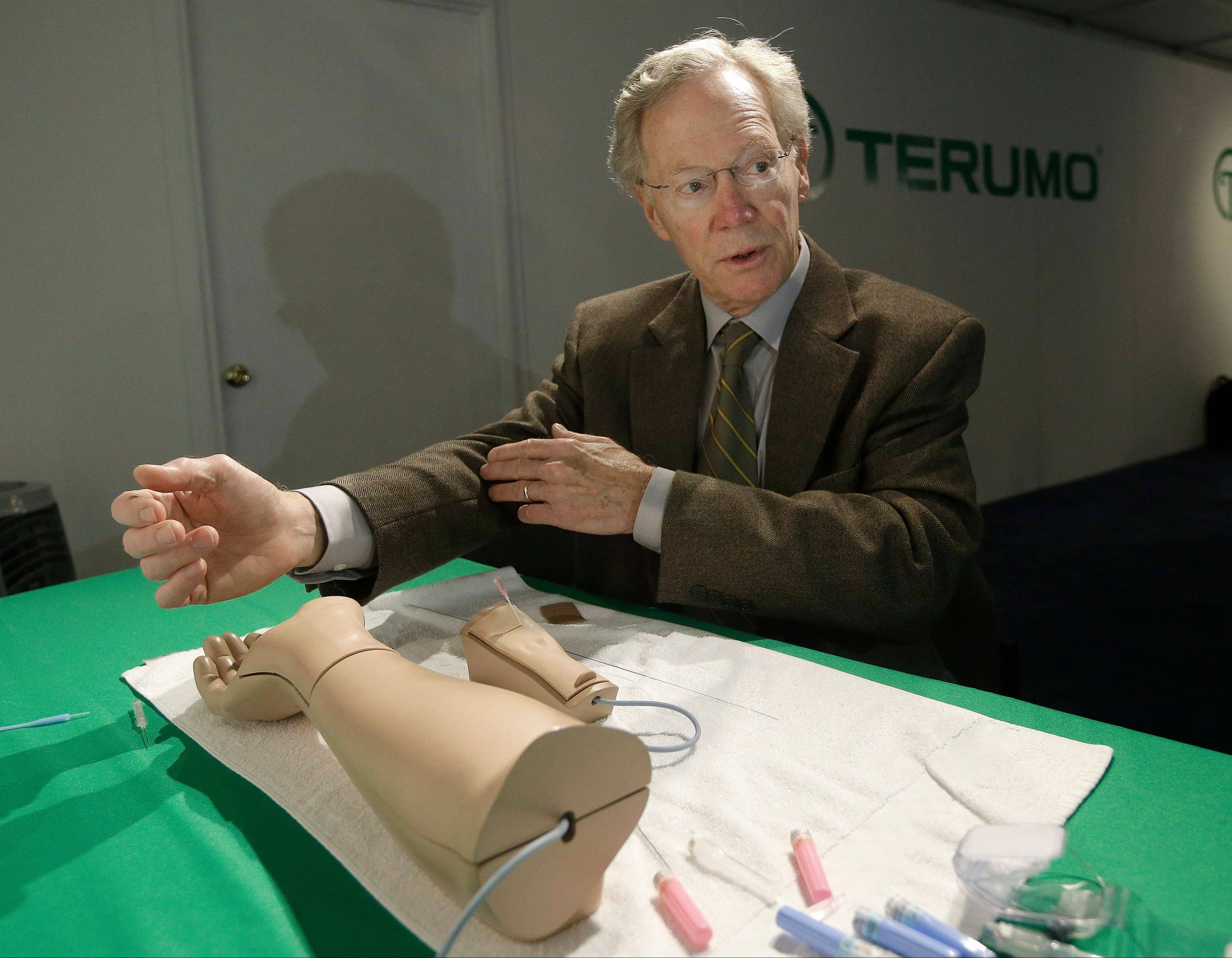 Cardiologist Dr. Spencer King demonstrates how doctors can open blocked heart arteries by going through an arm, using a model.