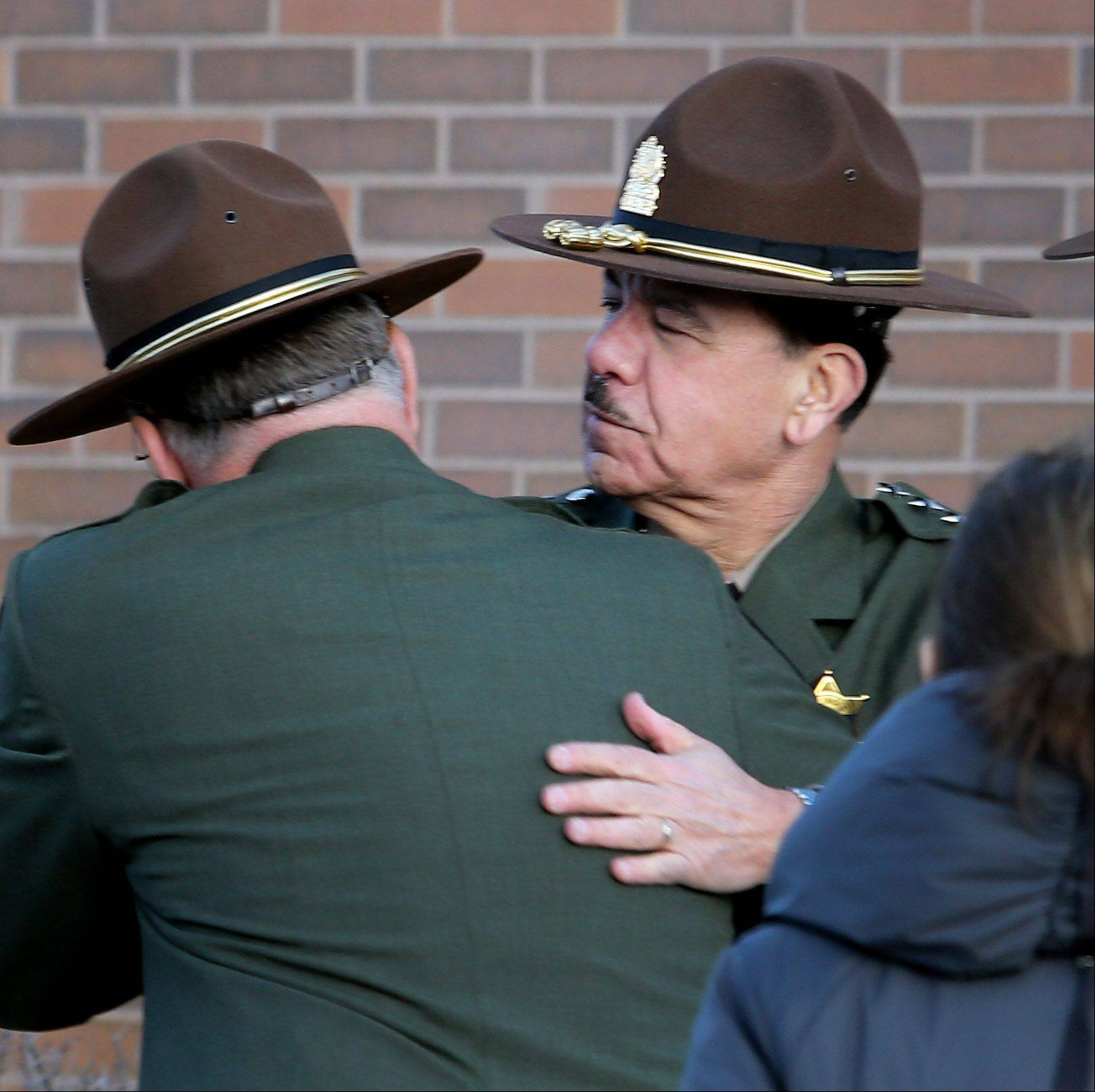 Hiram Grau, director of the Illinois State Police gives a hug to a trooper as mourners gather for the visitation of James Sauter at Moraine Valley Church in Palos Heights on Monday. He was an Illinois state trooper from Vernon Hills, who was killed early Friday morning on the job.