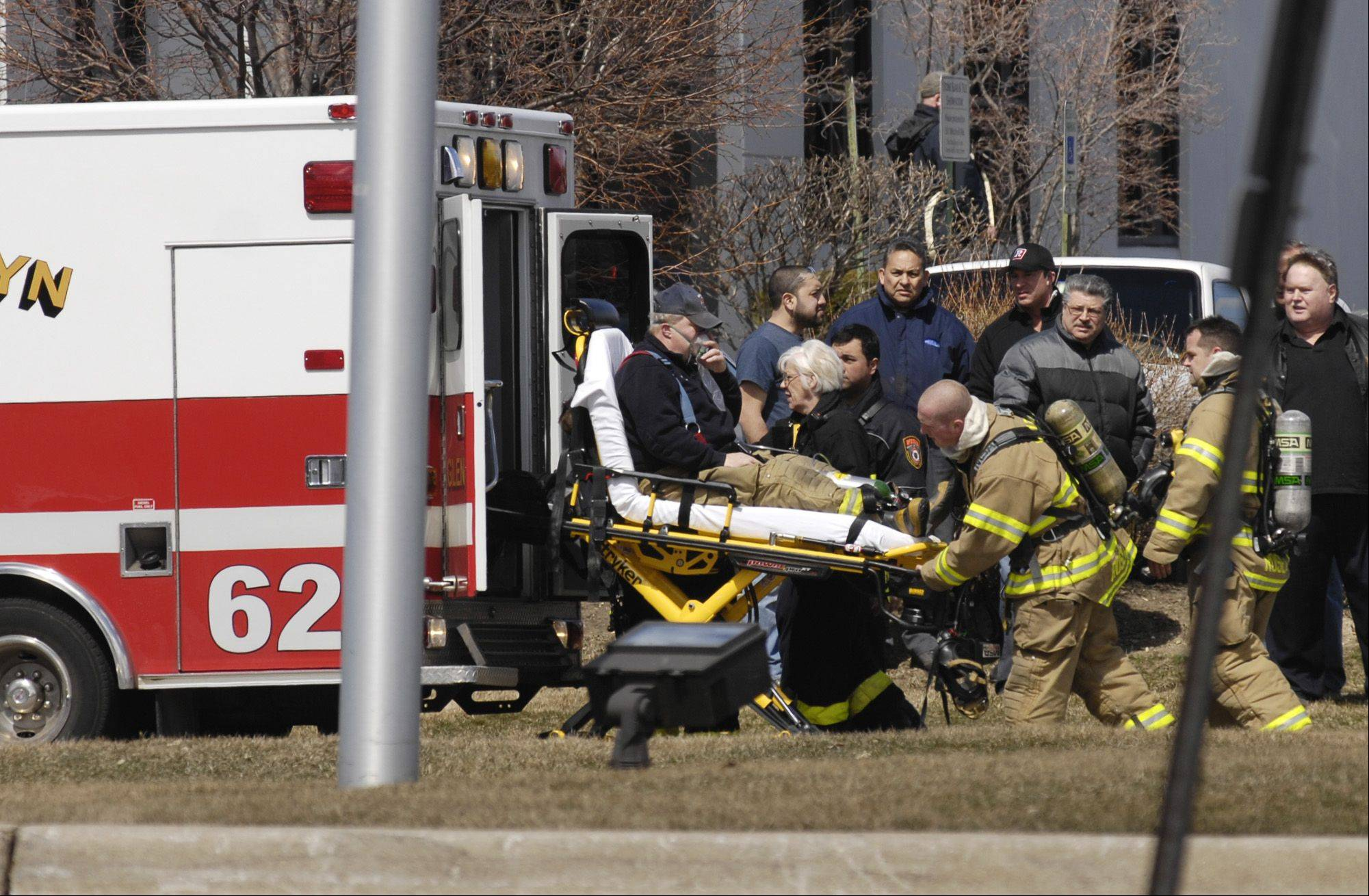 A firefighter is placed in an ambulance Monday as crews battle a fire and explosion at Northstar Metal Products Inc. in Glendale Heights.