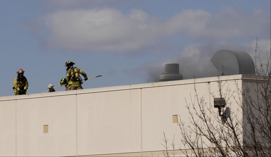 Firefighters work on the roof of Northstar Metal Products in Glendale Heights where an explosion and fire injured at least two people.