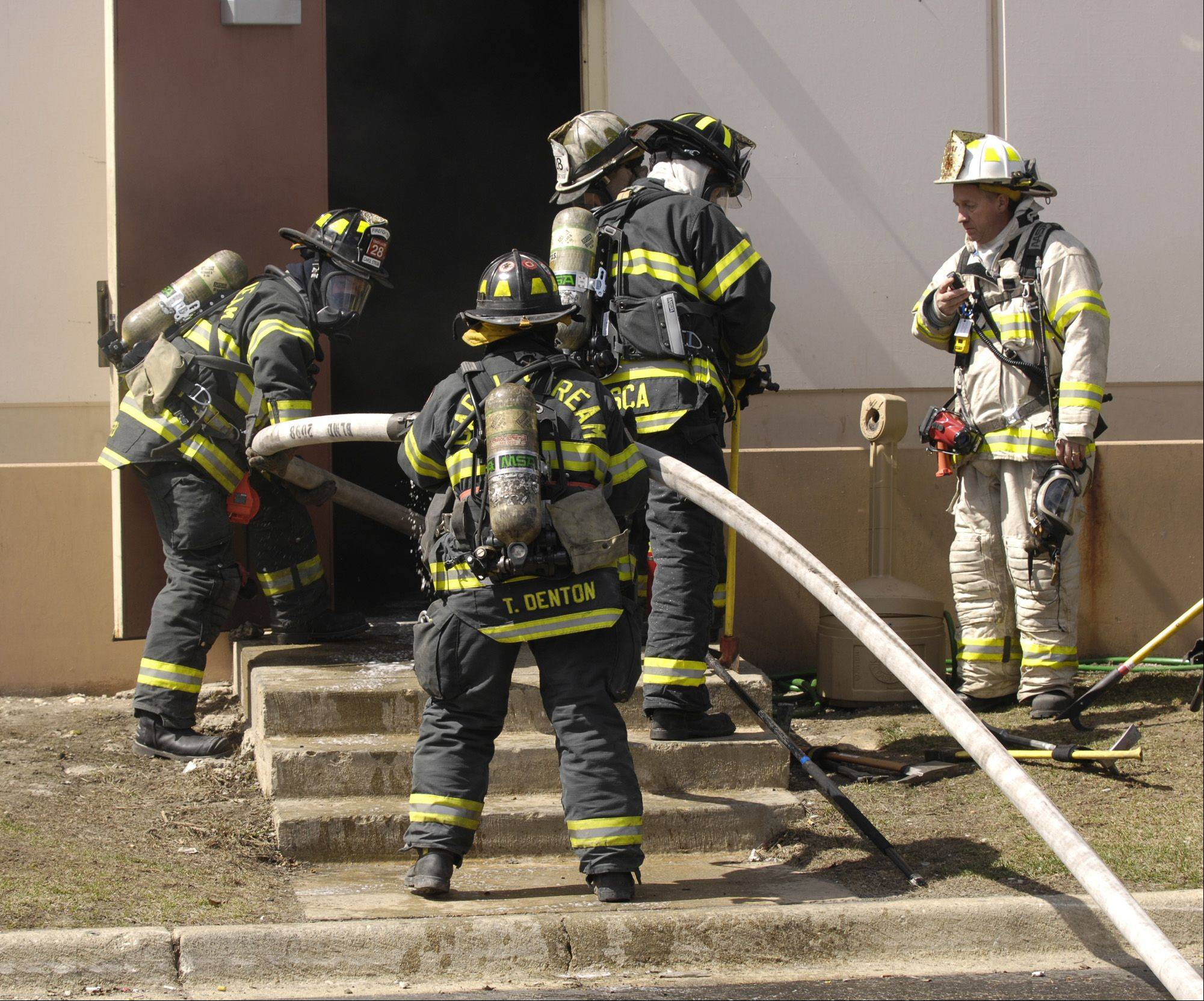 Firefighters pull a hose into the Northstar Metal Products Inc. building in Glendale Heights after an explosion sparked a fire and injured at least two people.