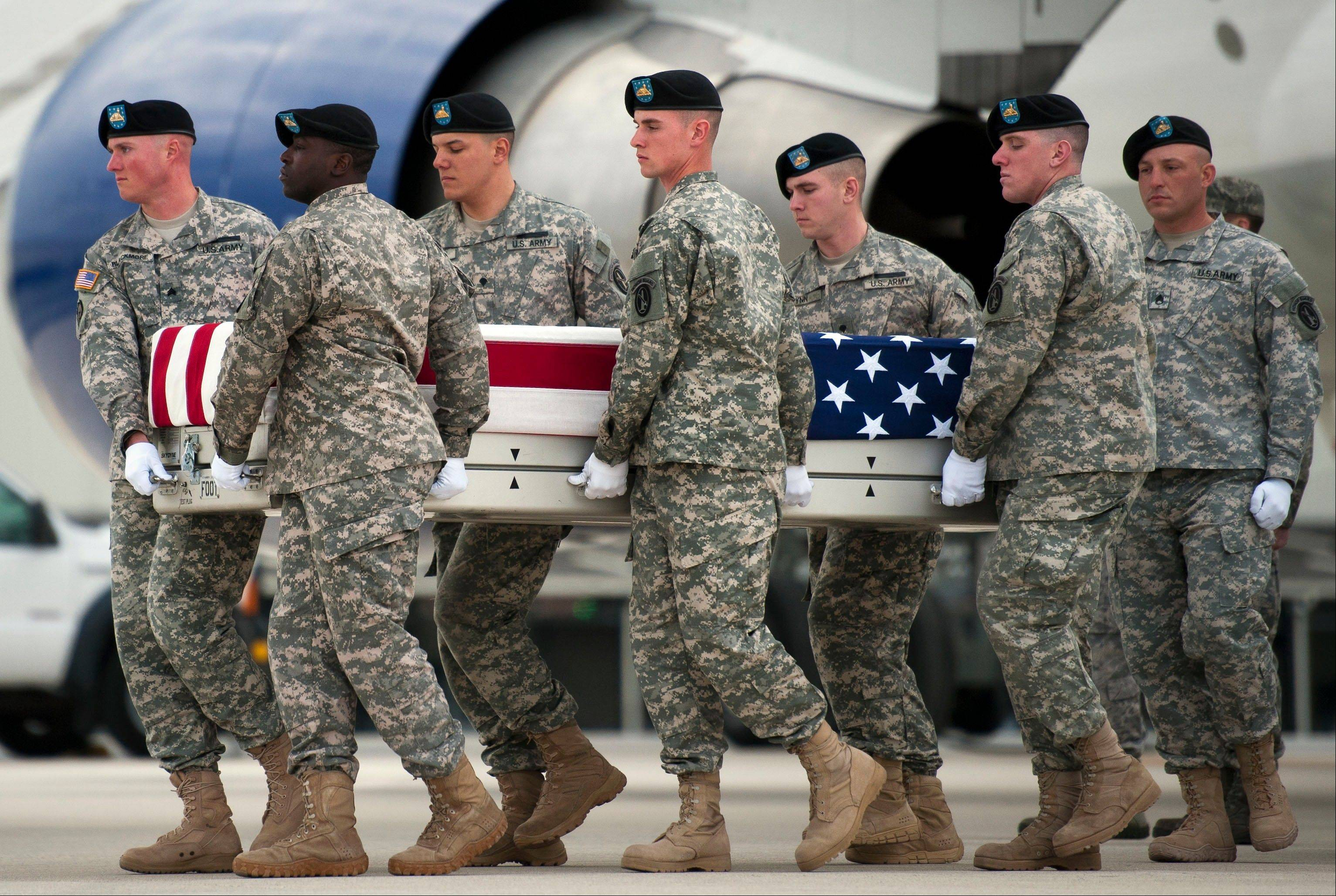 A U.S. Army carry team move a transfer case containing the remains of Army Sgt. Michael Cable, 26, of Philpot, Ky., at Dover Air Force Base, Del. An Afghan teenager killed Cable in eastern Afghanistan by stabbing him in the neck while he played with a group of local children, officials said Monday.