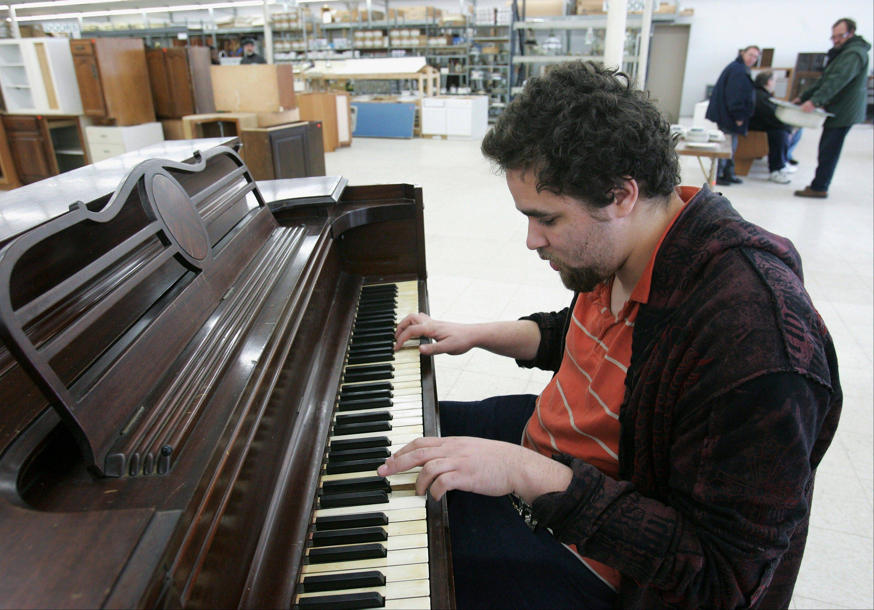 Elijah Londo, 22, who has Asperger syndrome, an autistic spectrum disorder, plays the piano at ReStore in Rockford, Ill. Londo used to work at ReStore, which benefits Rockford Area Habitat for Humanity. His foster mother J.