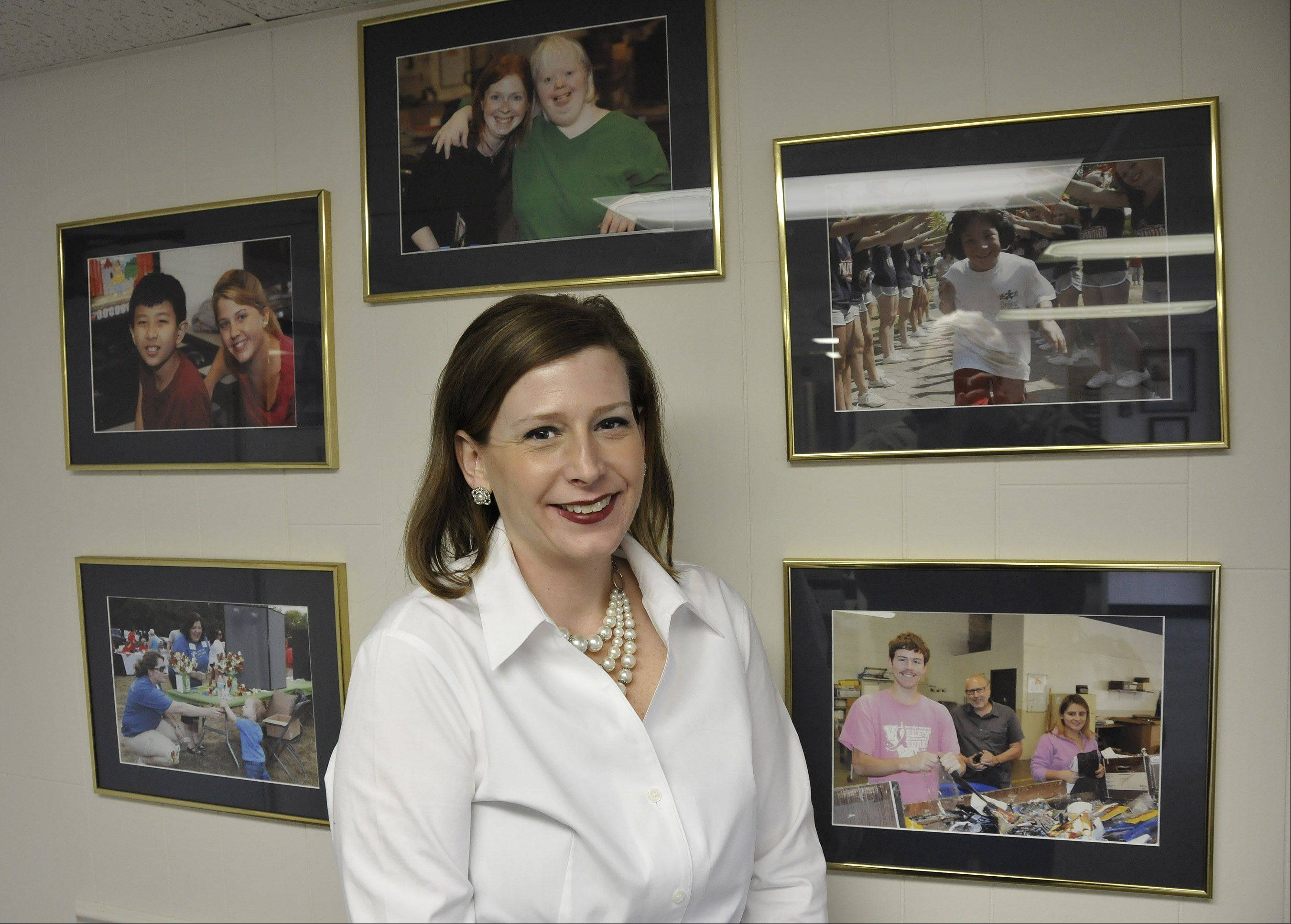 Kristi Landorf, the new CEO and president of Little Friends in Naperville, is surrounded by photos of clients who have autism or other developmental disabilities. Seeing their gains has been a source of great satisfaction, she said.