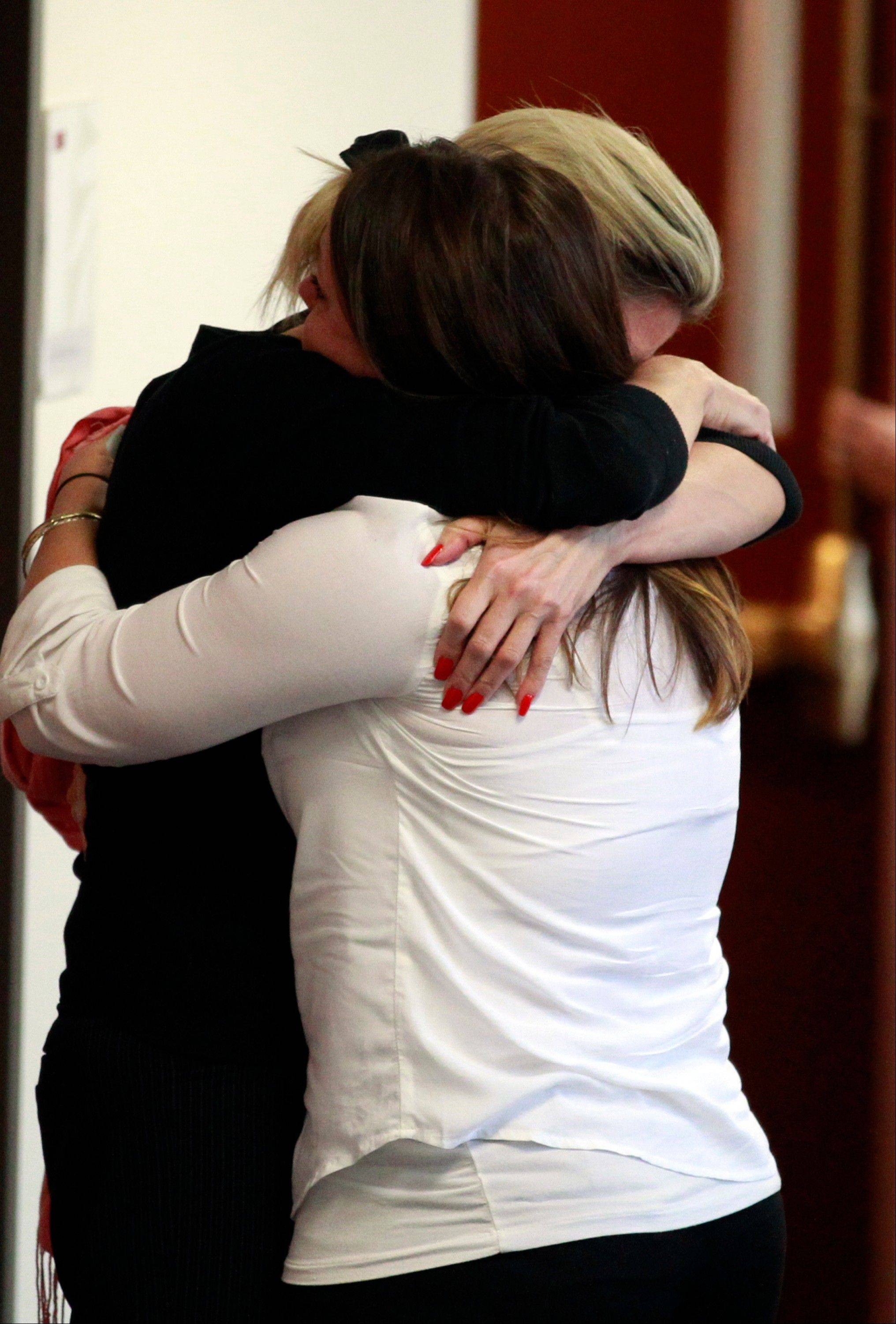 Unidentified women embrace outside of the courtroom in the case of Aurora theater shooting suspect James Holmes in Centennial, Colo., on Monday after hearing that the prosecution will seek the death penalty in the case against Holmes.