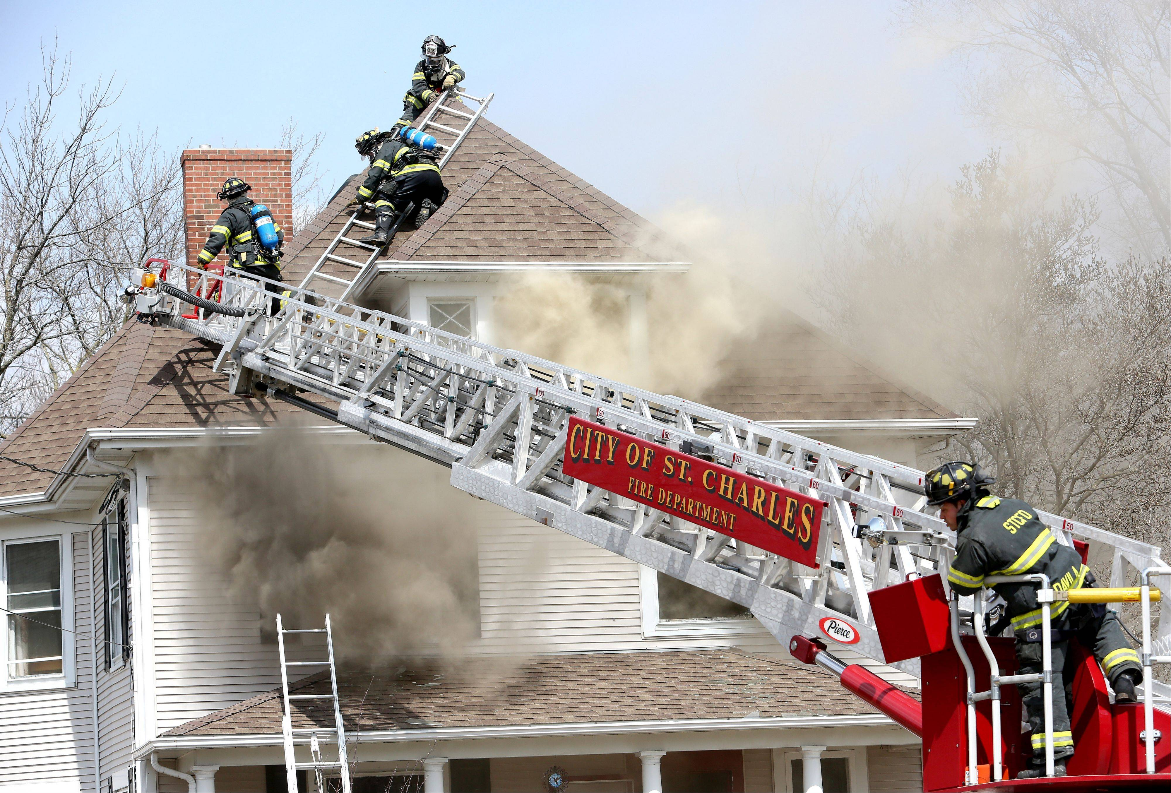 Firefighters battle a house fire in the 600 block of State Avenue in St. Charles on Sunday.