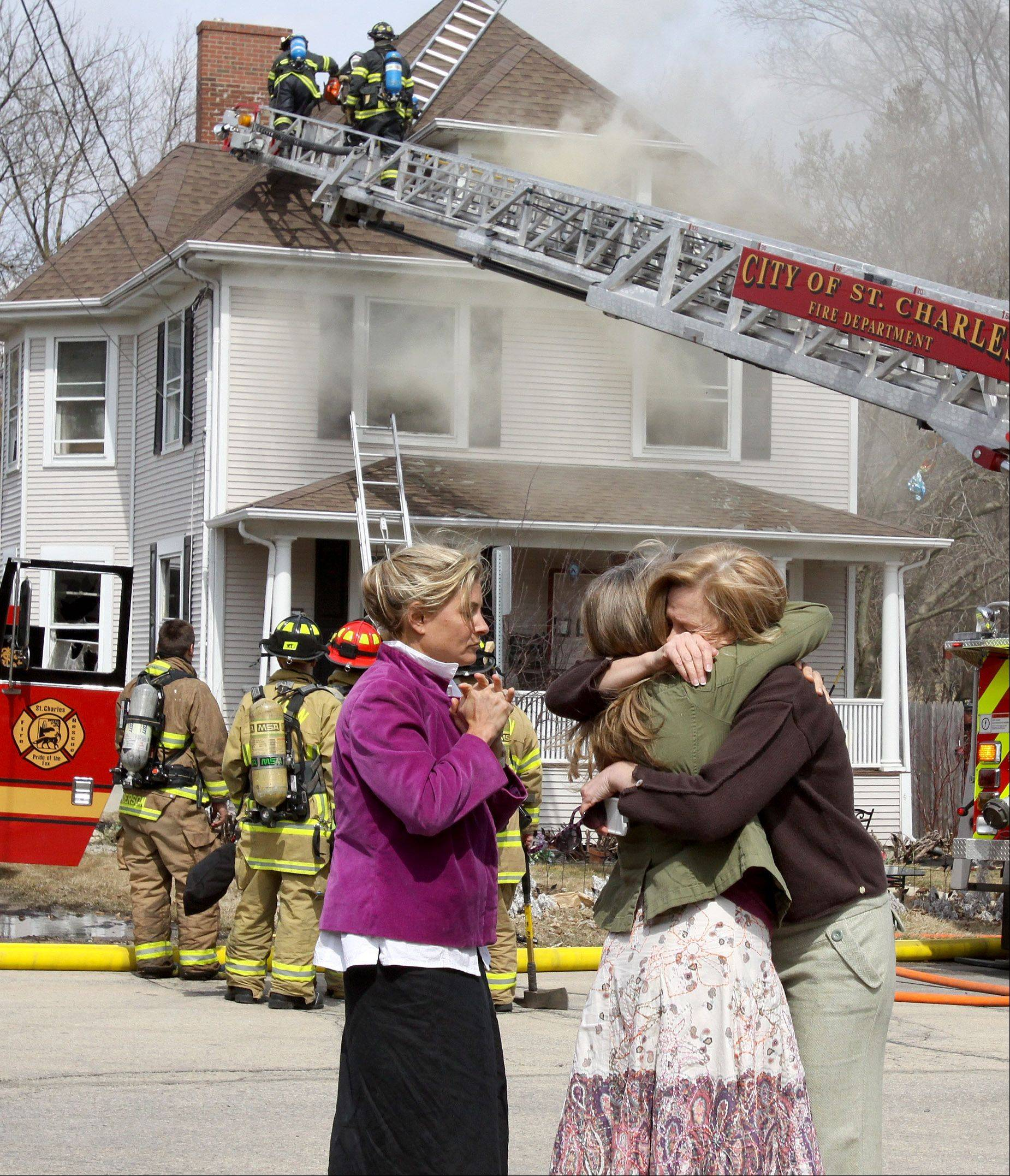 The homeowner, right, is comforted by friends as firefighters battle a fire at her house and business in the 600 block of State Avenue in St. Charles on Sunday.