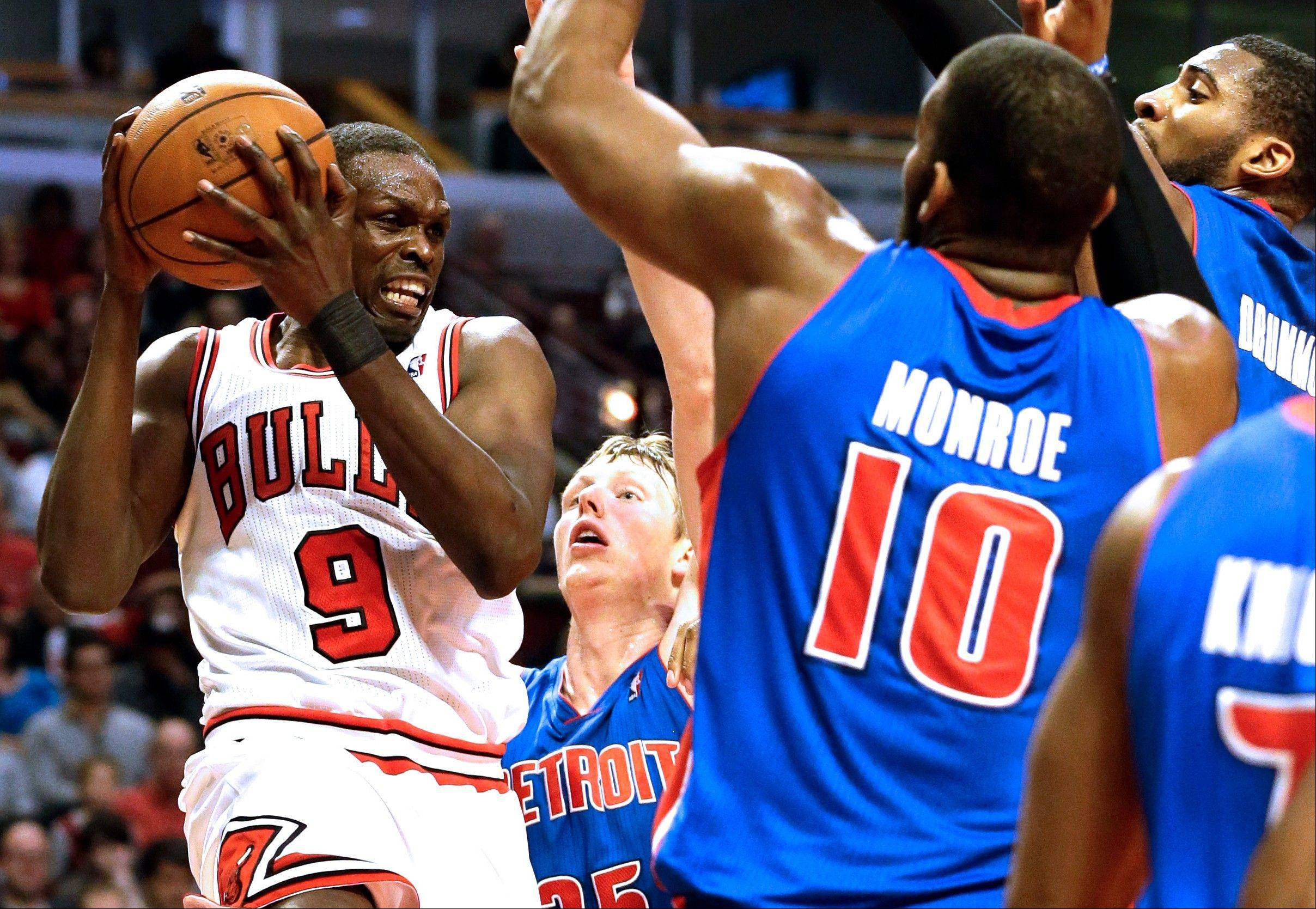 Bulls forward Luol Deng, left, drives to the basket against Detroit Pistons defenders including Greg Monroe during the second half of an NBA basketball game in Chicago on Sunday, March 31, 2013. The Bulls won 95-94.