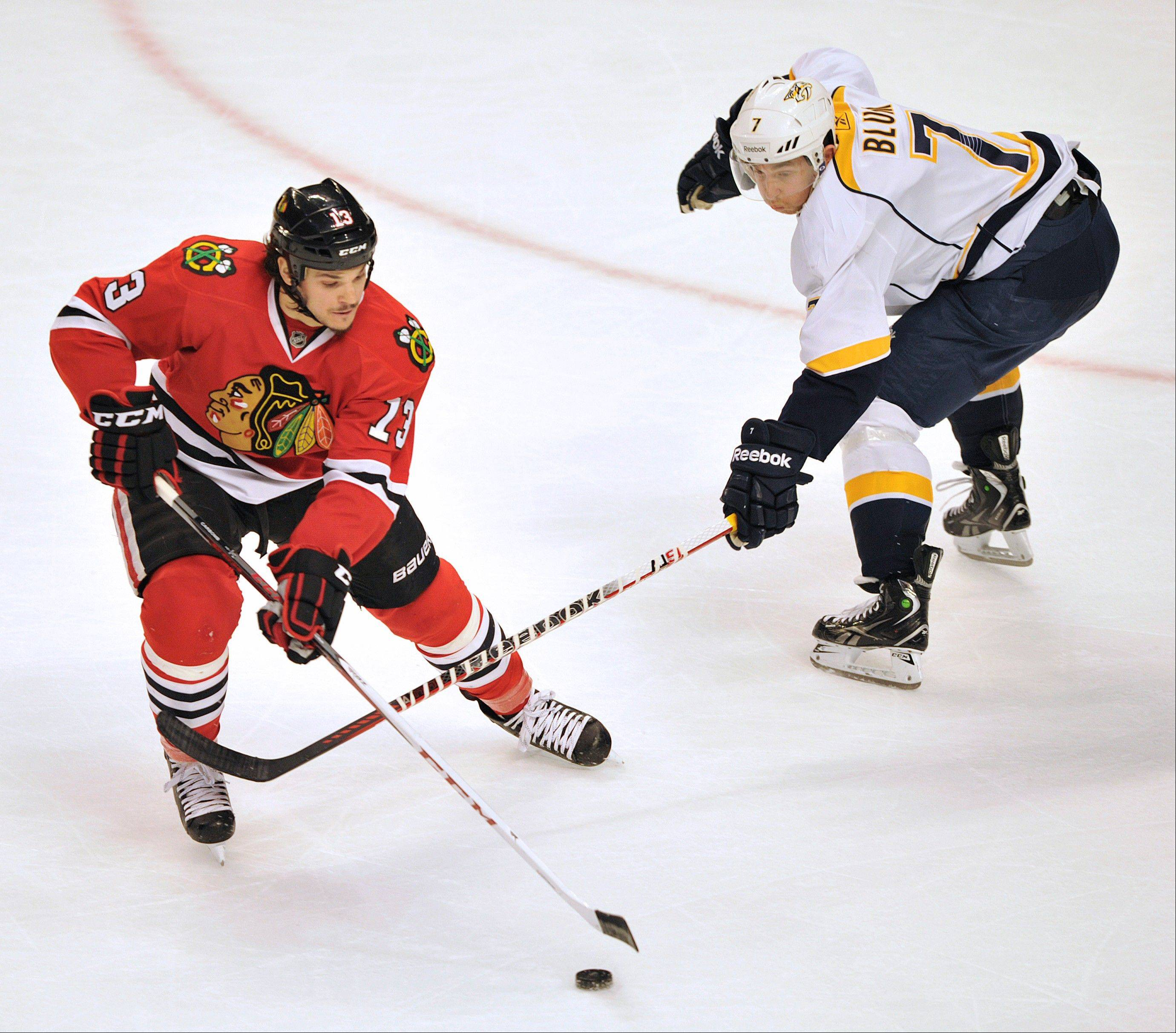 Chicago Blackhawks' Daniel Carcillo (13) keeps the puck away from Nashville Predators' Jonathon Blum during the second period.