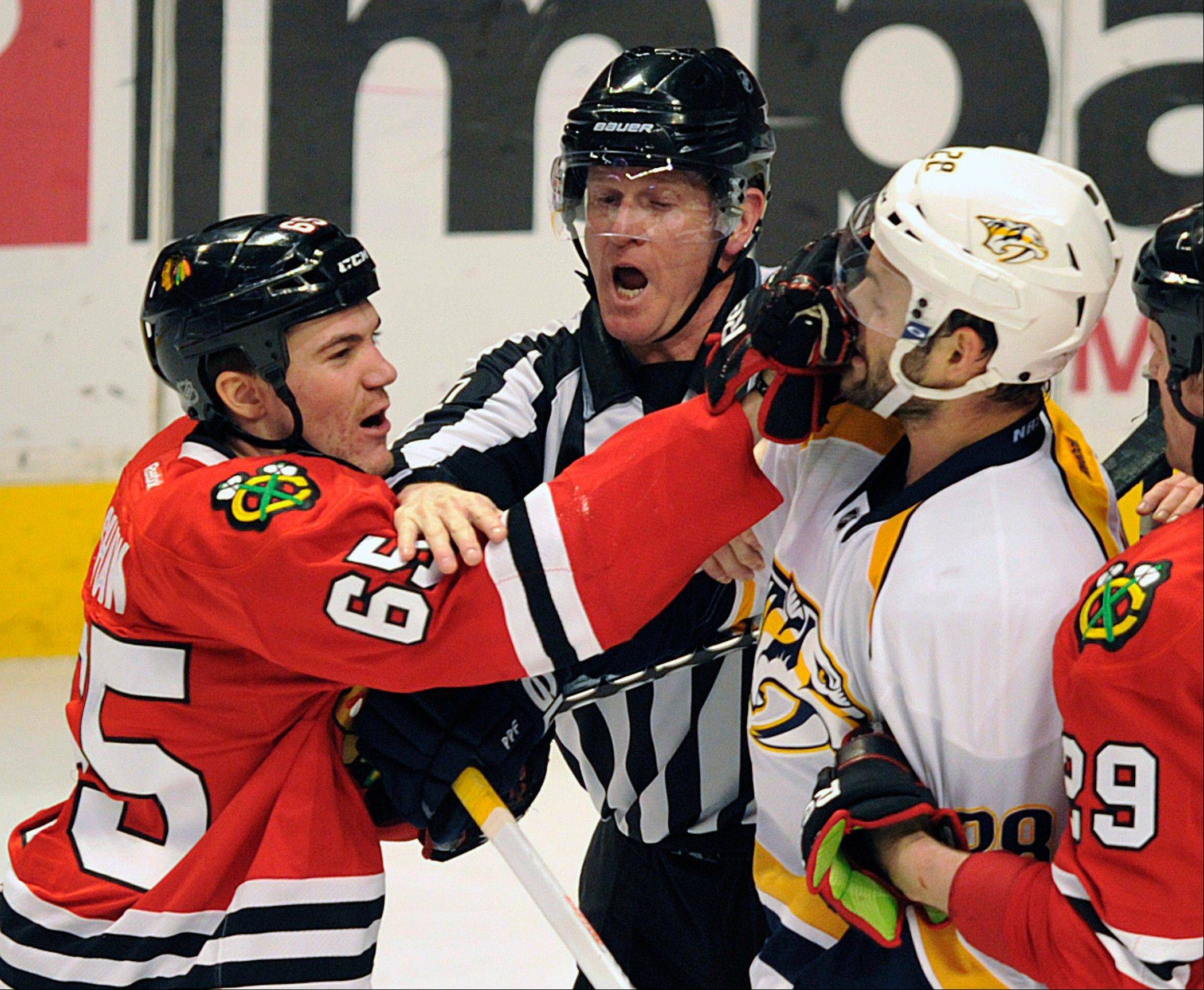 Chicago Blackhawks' Andrew Shaw (65) punches Nashville Predators' Paul Gaustad during a fight in the second period.