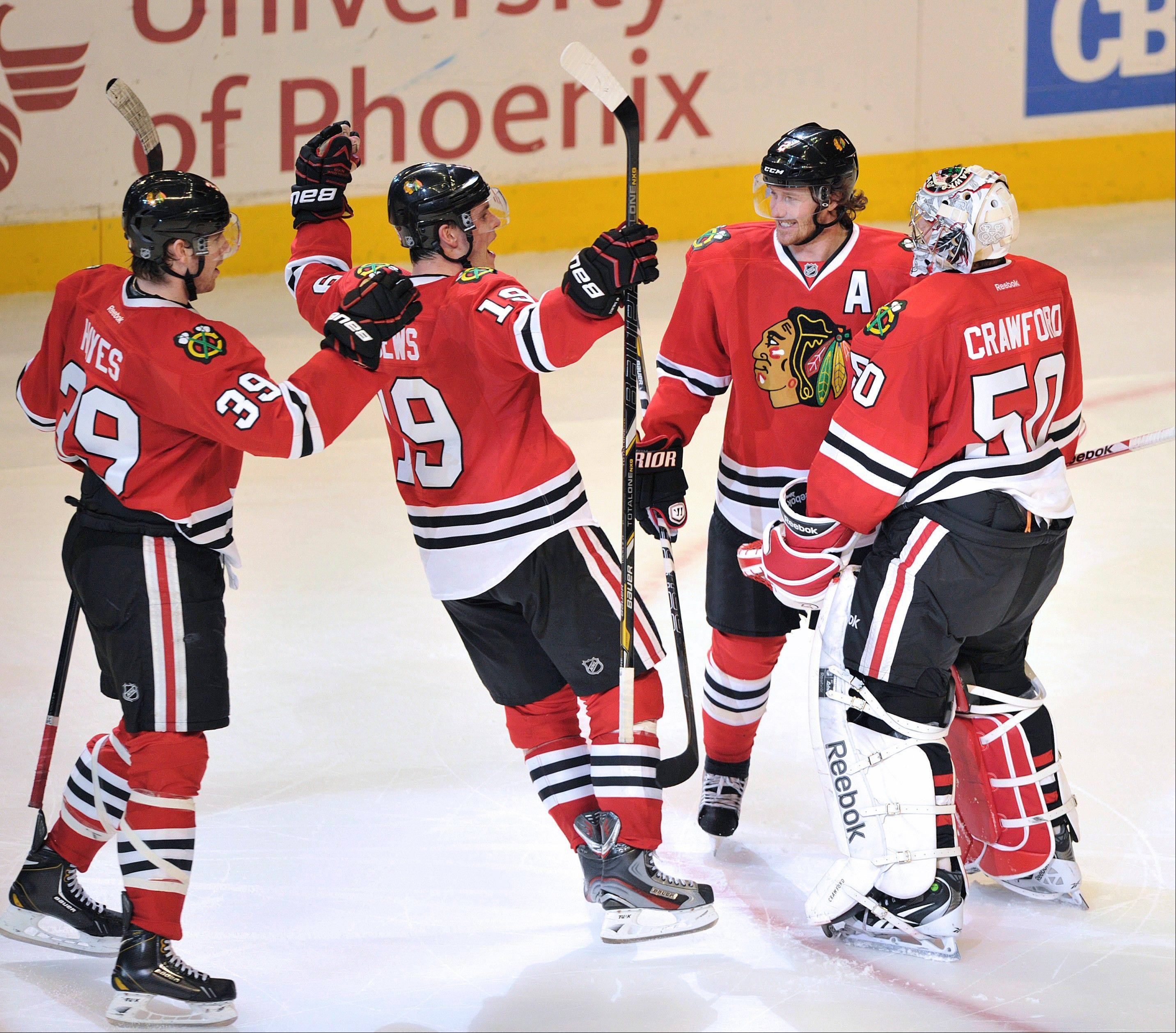 Chicago Blackhawks' Jimmy Hayes (39), Jonathan Toews, and Duncan Keith celebrate with Corey Crawford (50) after a 3-2 shoot out victory.