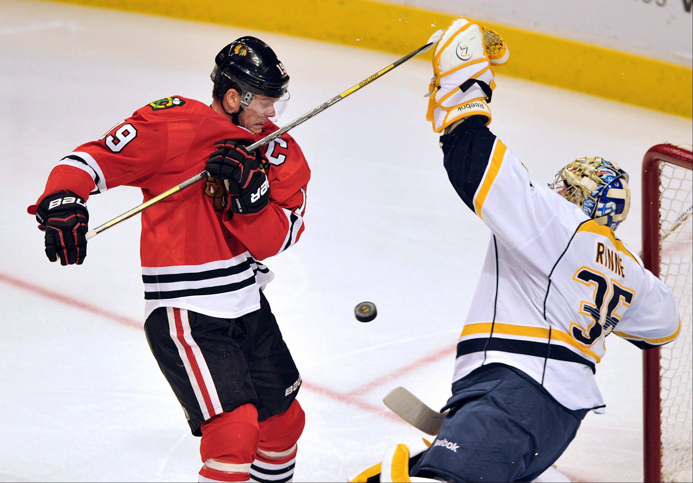 Chicago Blackhawks' Jonathan Toews, left, tries to tip in the puck as Nashville Predators' Pekka Rinne (35) blocks the shot during the second period.