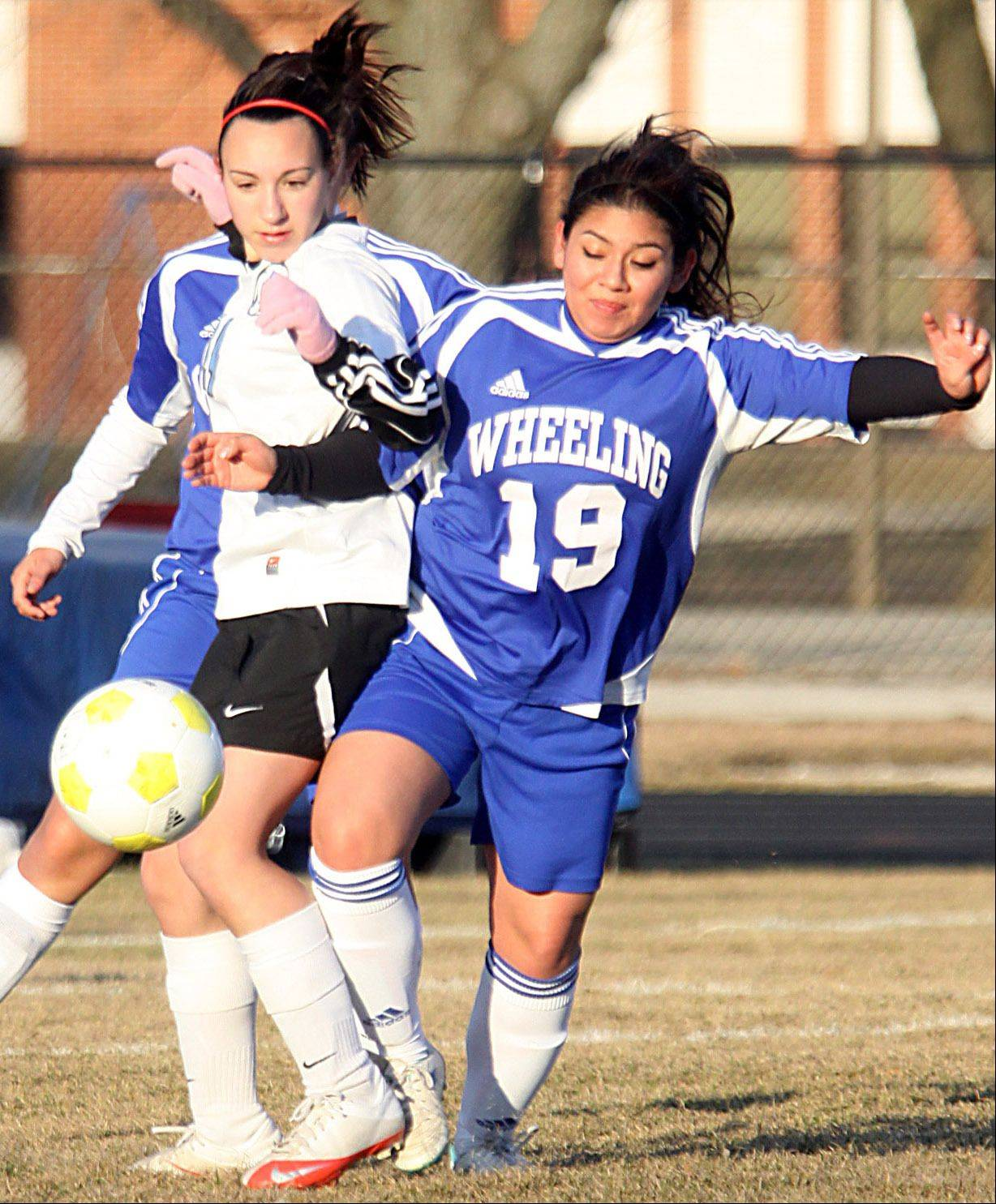 Wheeling's CeCe Estrada, right, and Maine West's Alice Faraone, left, pursue the ball on Monday in Des Plaines.