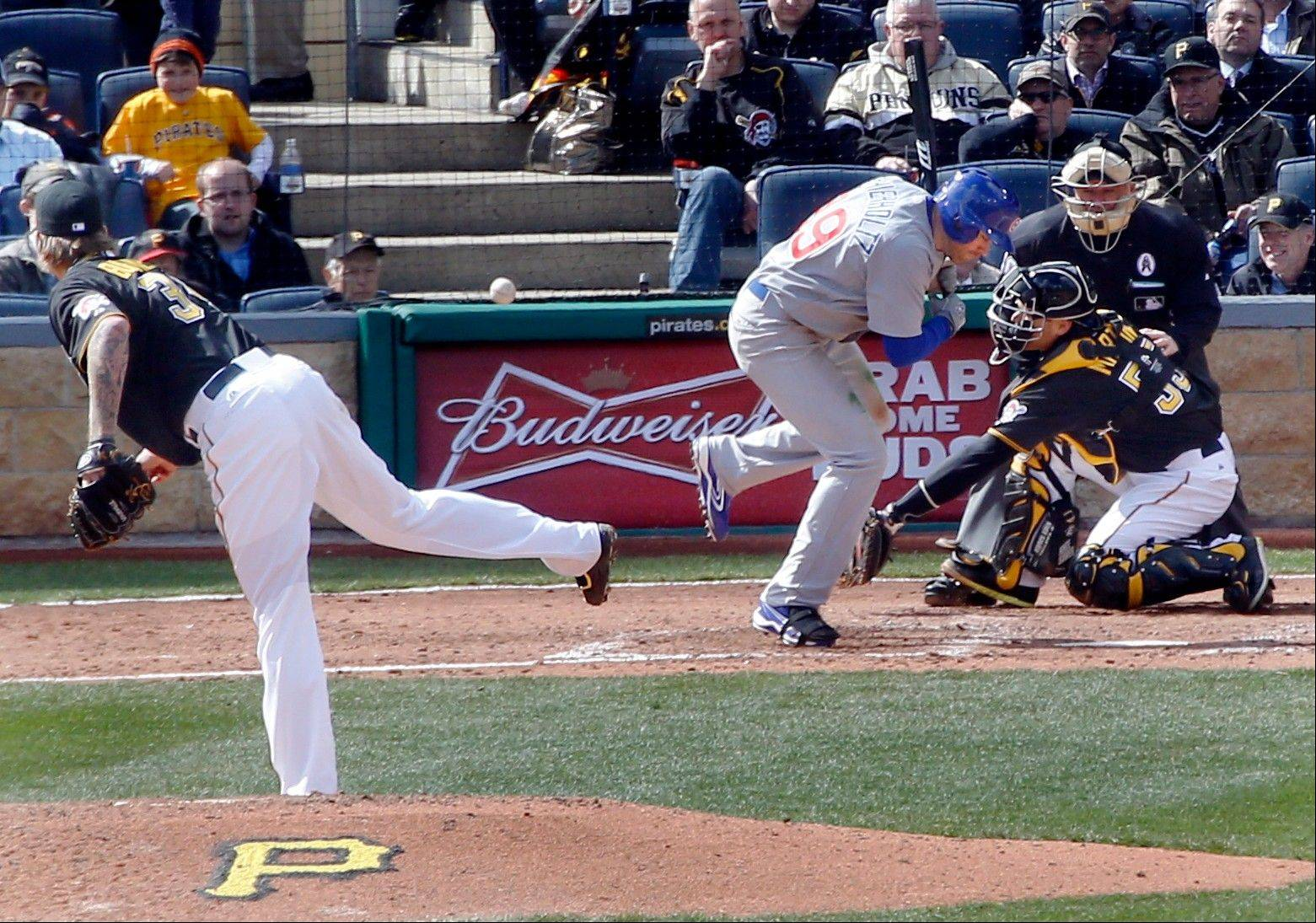 Chicago Cubs' Nate Schierholtz, center, skips after being hit by a pitch by Pittsburgh Pirates starting pitcher A.J. Burnett, left, in the sixth inning .