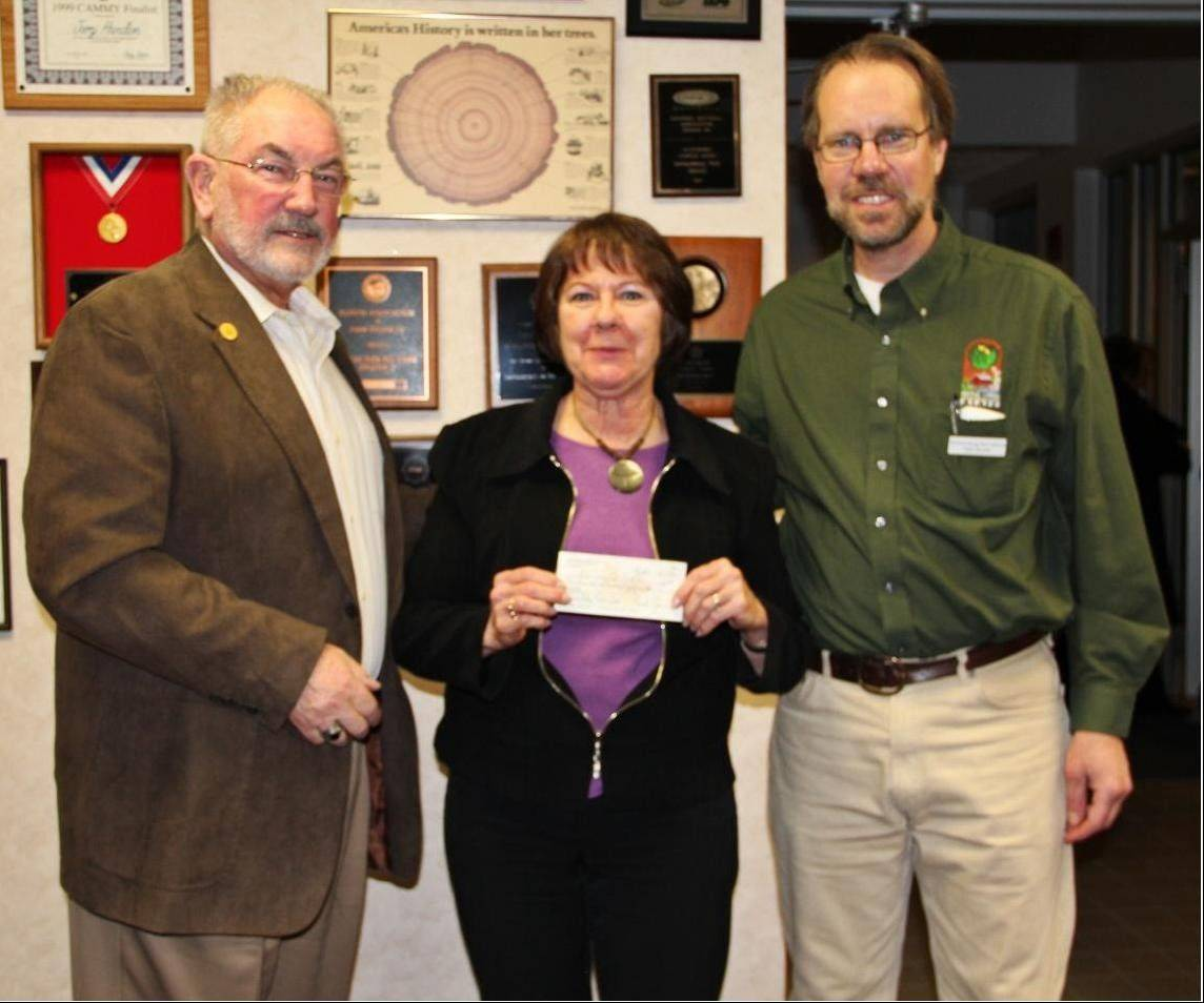 Schaumburg Community Garden Club's Jan Doud presents a check to Park Board President Bob Schmidt and Dave Brooks, manager of conservation services.
