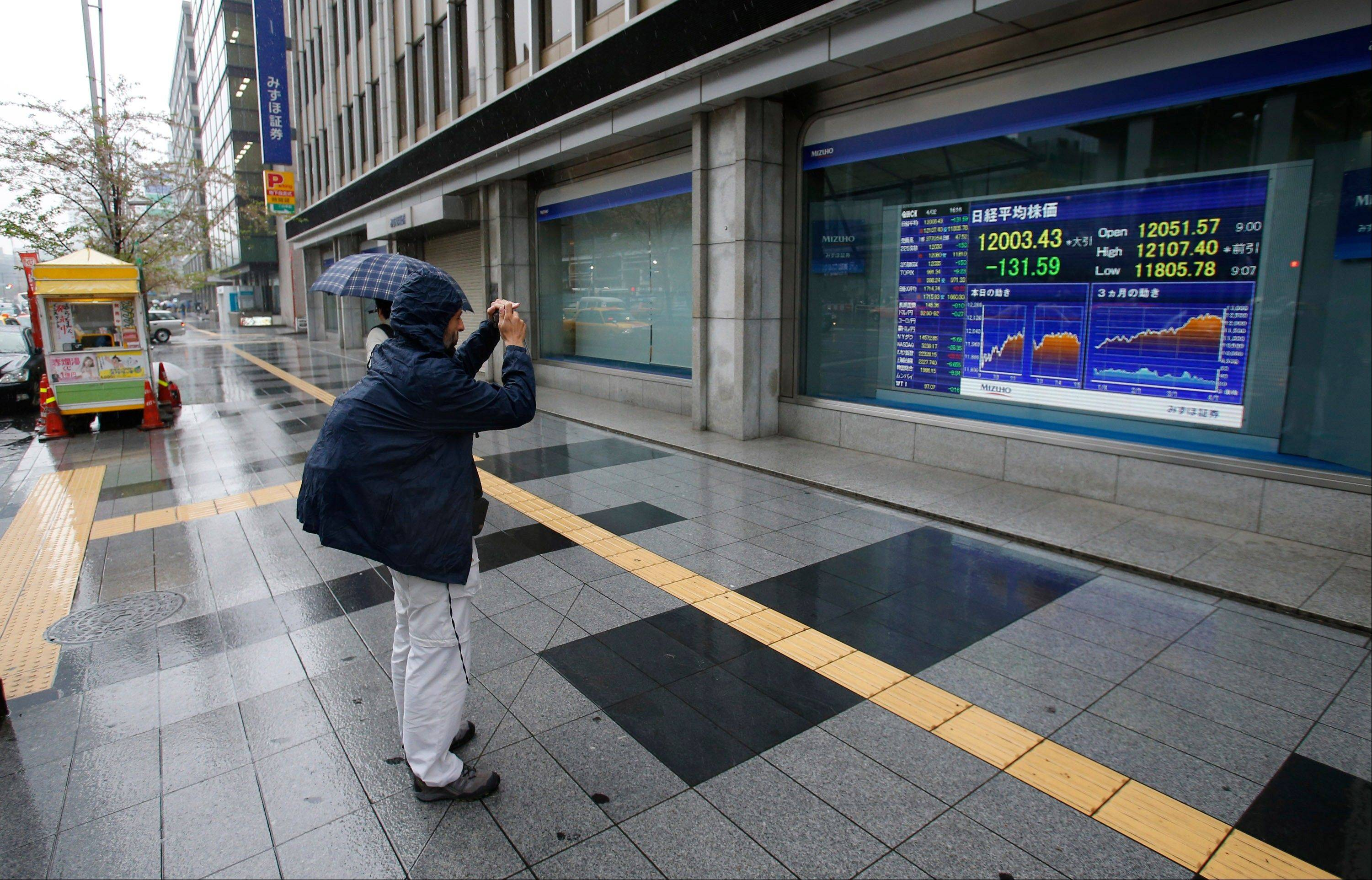 A man takes a picture of an electronic stock indicator in Tokyo, Japan, Tuesday.